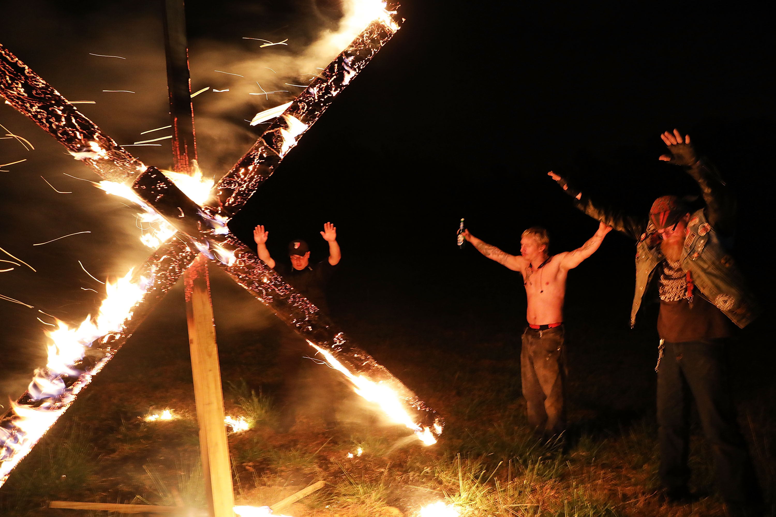 Members of the National Socialist Movement, one of the largest neo-Nazi groups in the US, hold a swastika burning after a rally on April 21, 2018 in Draketown, Georgia. Community members had opposed the rally in Newnan and came out to embrace racial unity in the small Georgia town. Fearing a repeat of the violence that broke out after Charlottesville, hundreds of police officers were stationed in the town during the rally in an attempt to keep the anti racist protesters and neo-Nazi groups separated