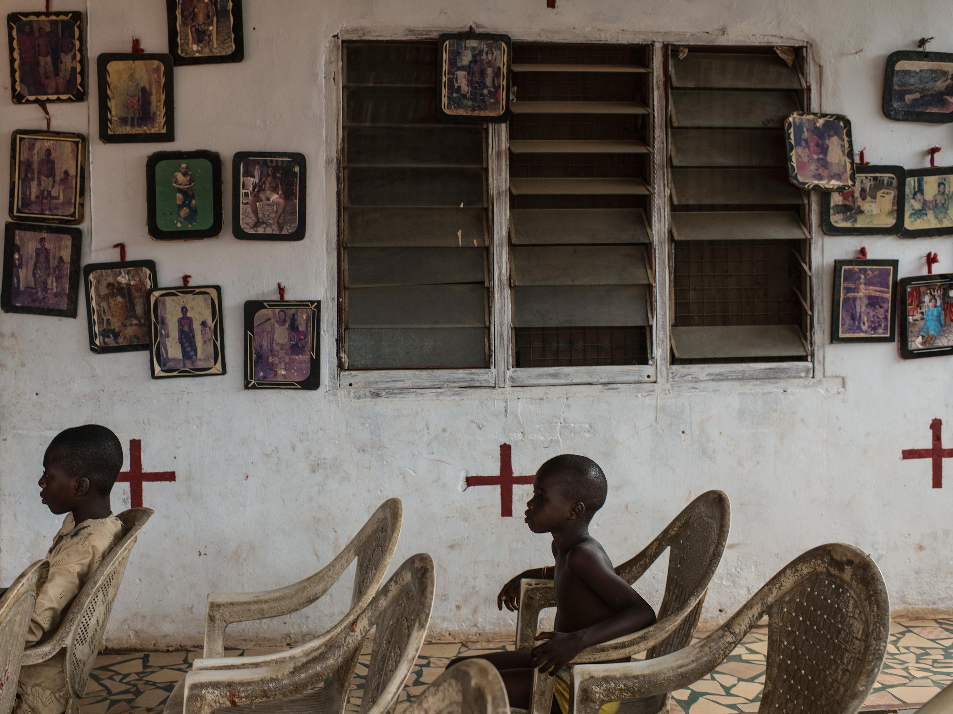 Children watch Ayelala Juju priest Godwin Okeh at his shrine in Benin City on March 23.