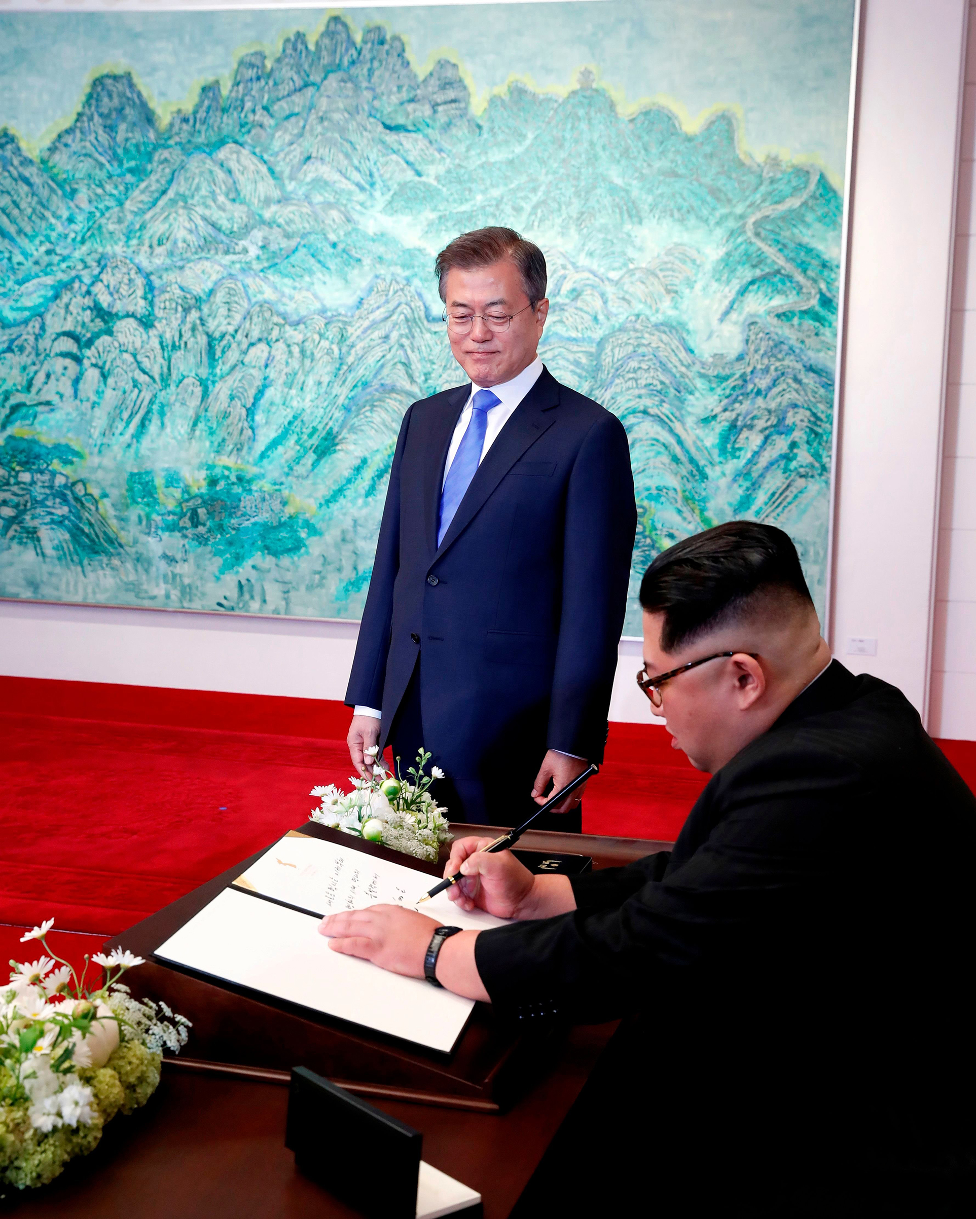 North Korean leader Kim Jong-Un (R) signs his name in the visitors' book before an inter-Korean summit with South Korean President Moon Jae-In at the Peace House at the south side of the truce village of Panmunjom in the demilitarized zone