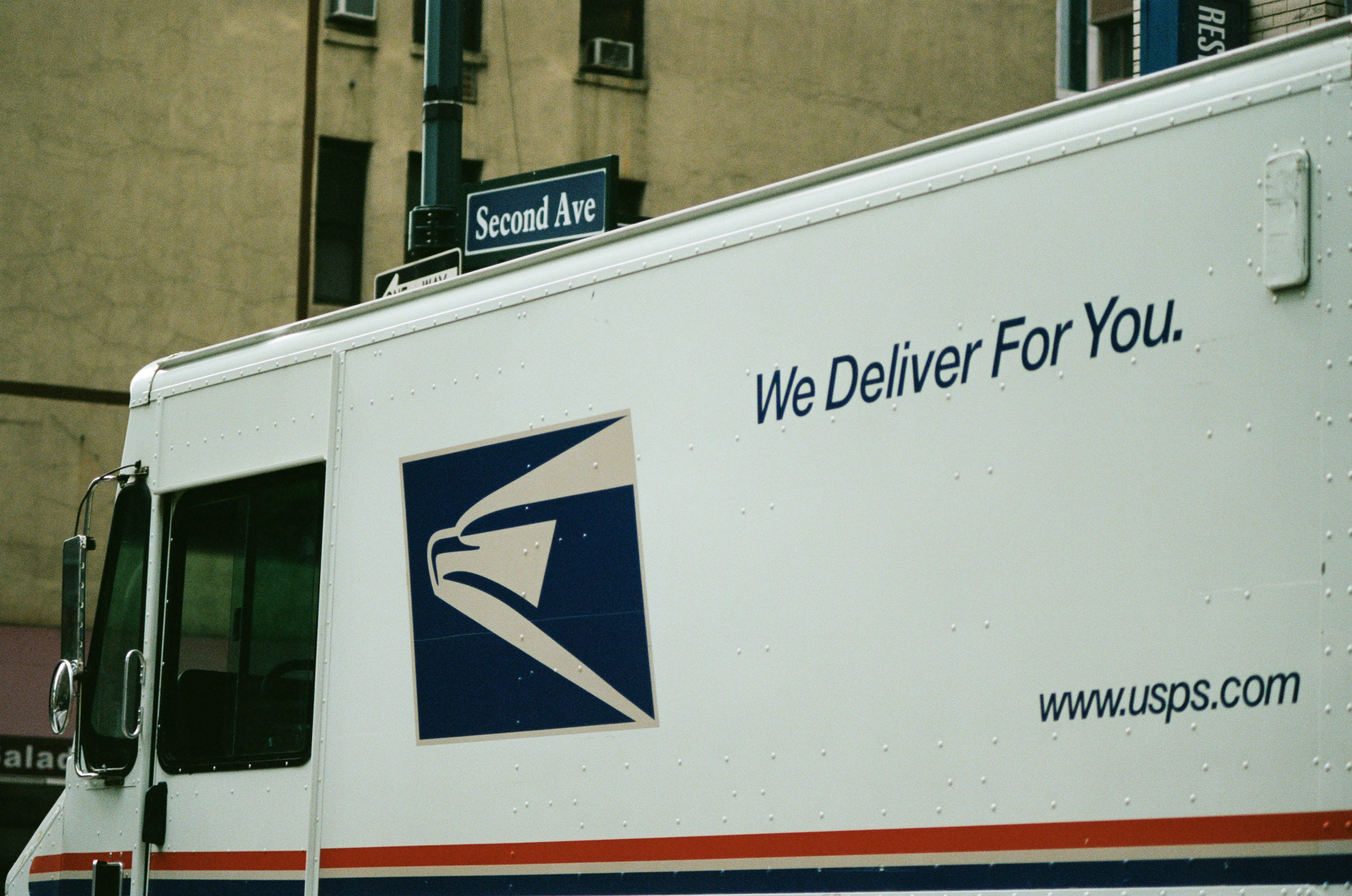 Close-up of logo on a United States Postal Service (USPS) mail truck with tagline reading 'We Deliver For You' driving down 2nd Avenue in Manhattan, New York City, New York, September 15, 2017.