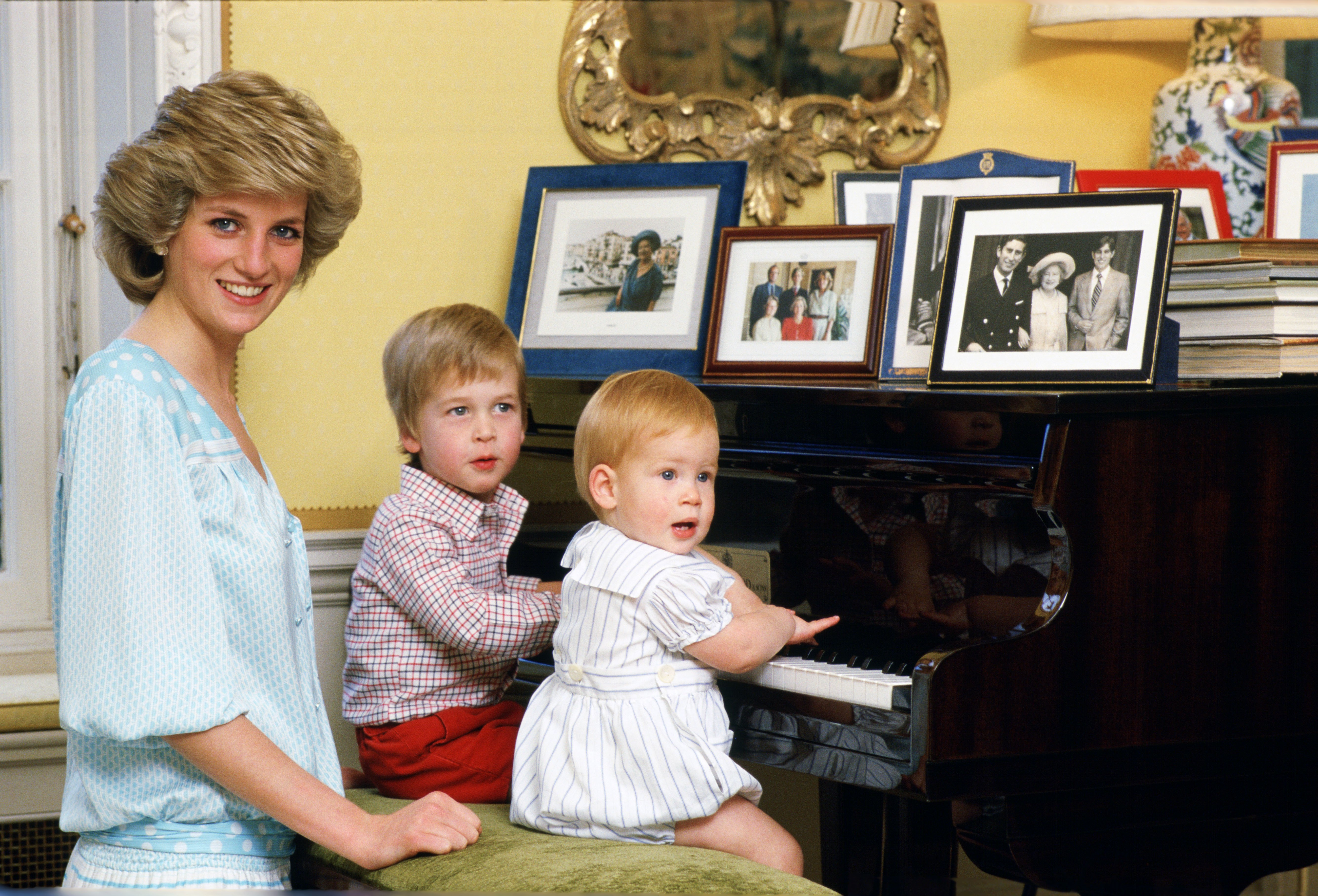 Diana, Princess of Wales with her sons, Prince William and Prince Harry, at the piano in Kensington Palace.