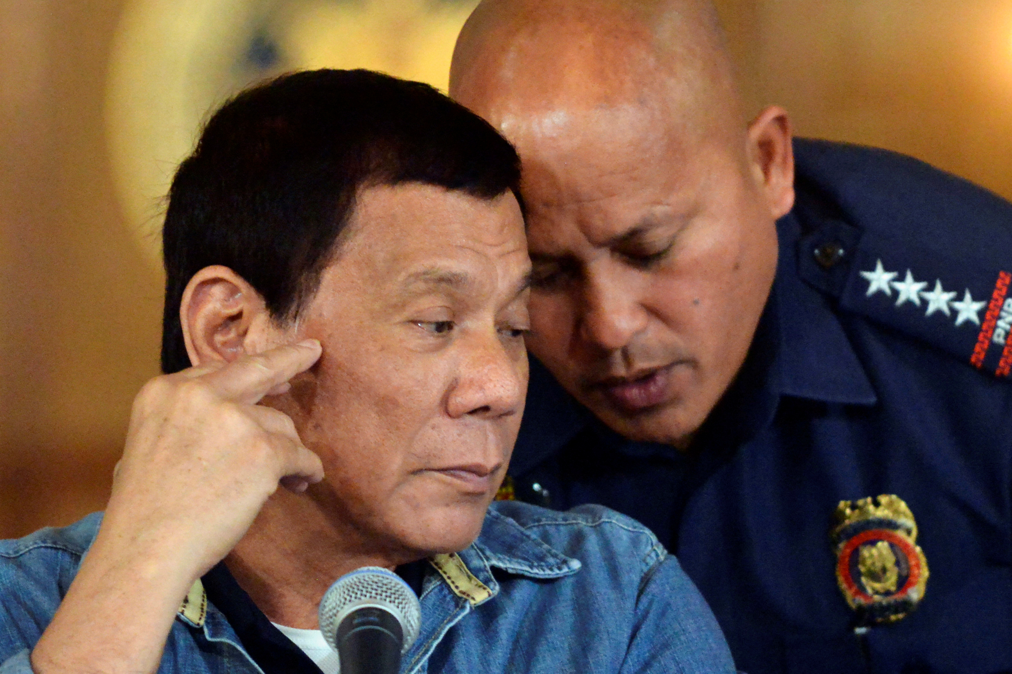 Philippine President Rodrigo Duterte listens to Philippine National Police (PNP) Director General Ronald Dela Rosa at the presidential palace in Manila, Philippines on Jan. 29, 2017.