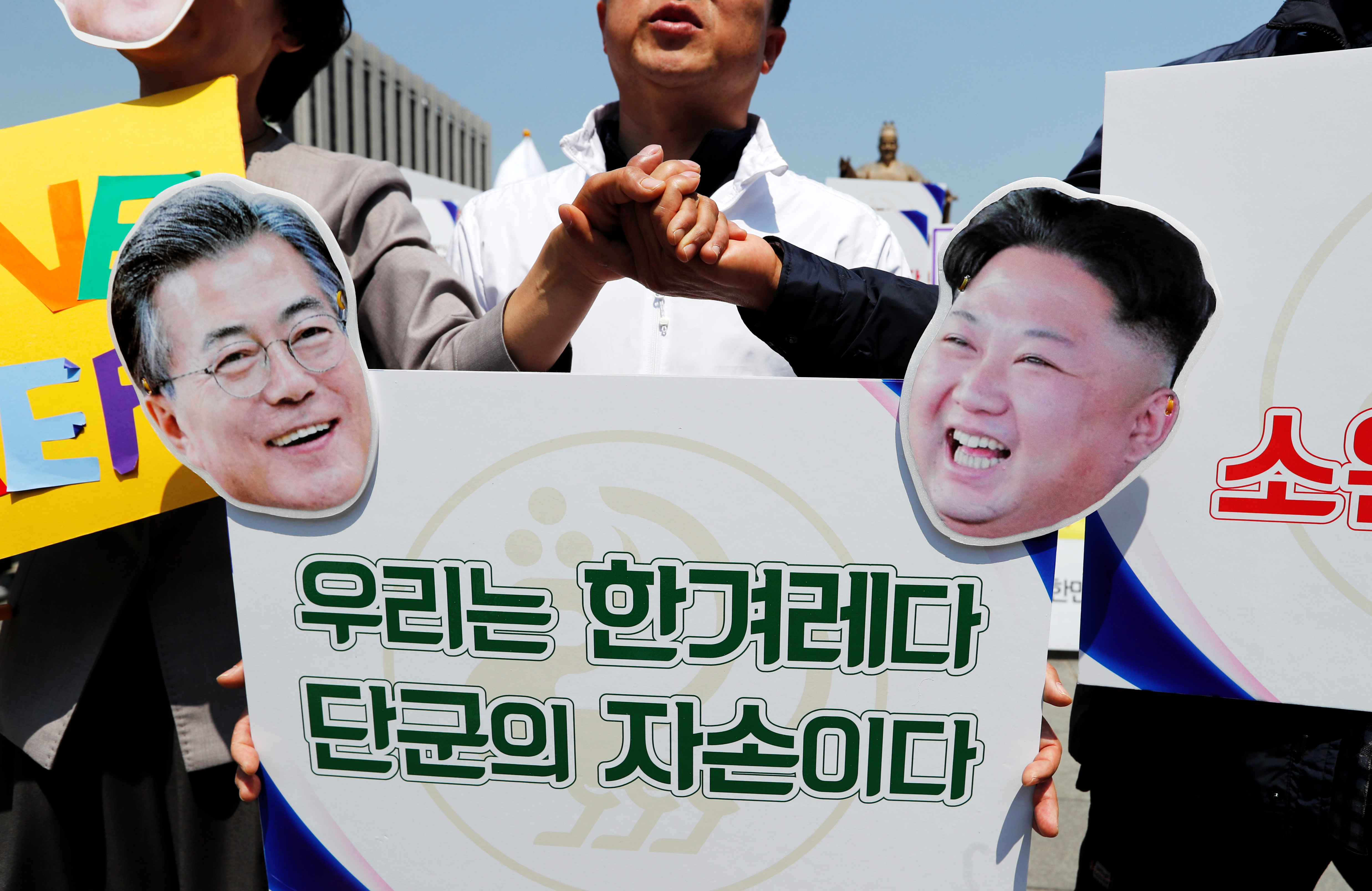People hold hands behind a sign with cutouts of South Korea's President Moon Jae-in and North Korea's leader Kim Jong Un ahead of the upcoming summit between North and South Korea in Seoul, April 25.