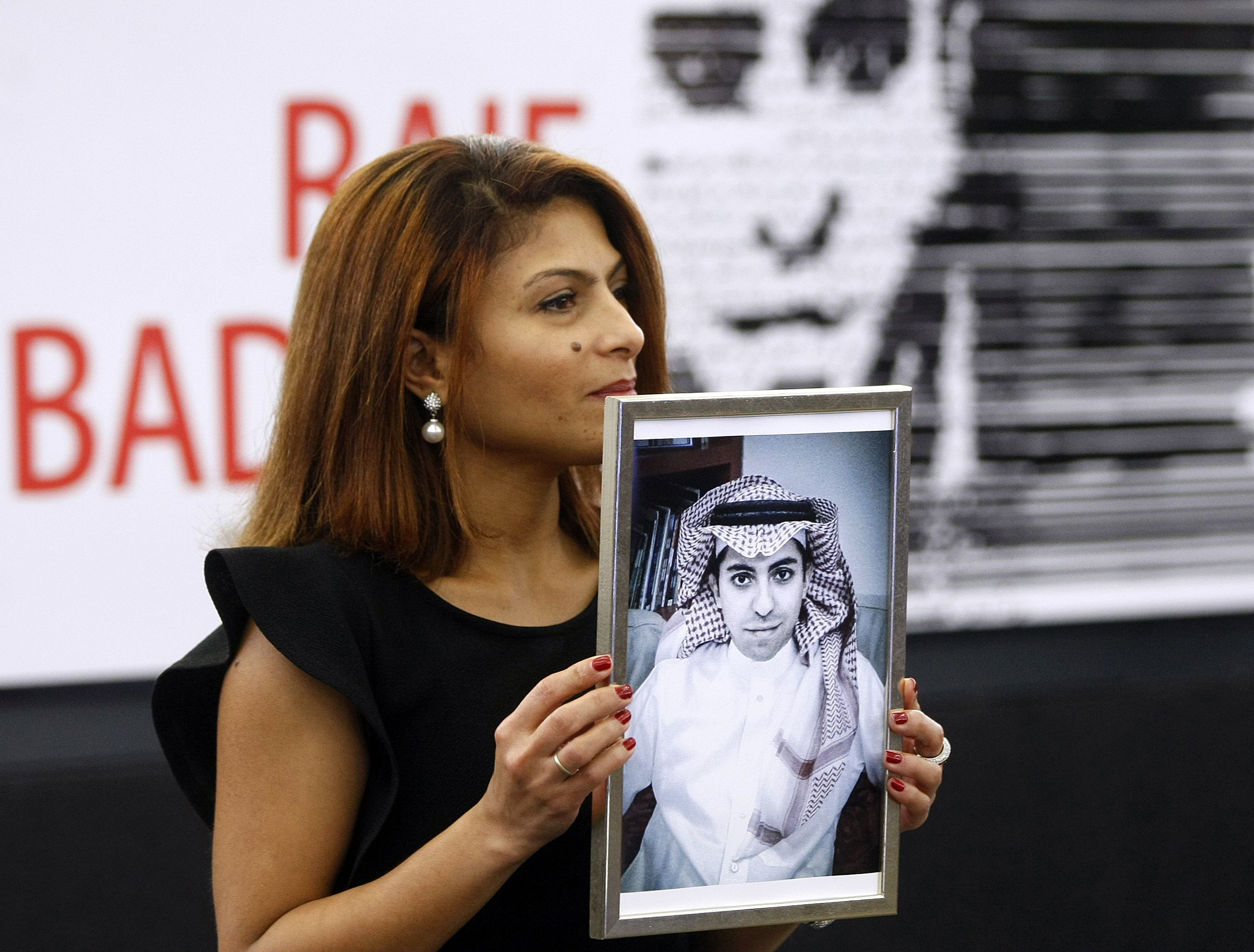 Ensaf Haidar, wife of the jailed Saudi Arabian blogger Raif Badawi, shows a portrait of her husband as he is awarded with the Sakharov Prize, on Dec. 16, 2015 in Strasbourg, France.