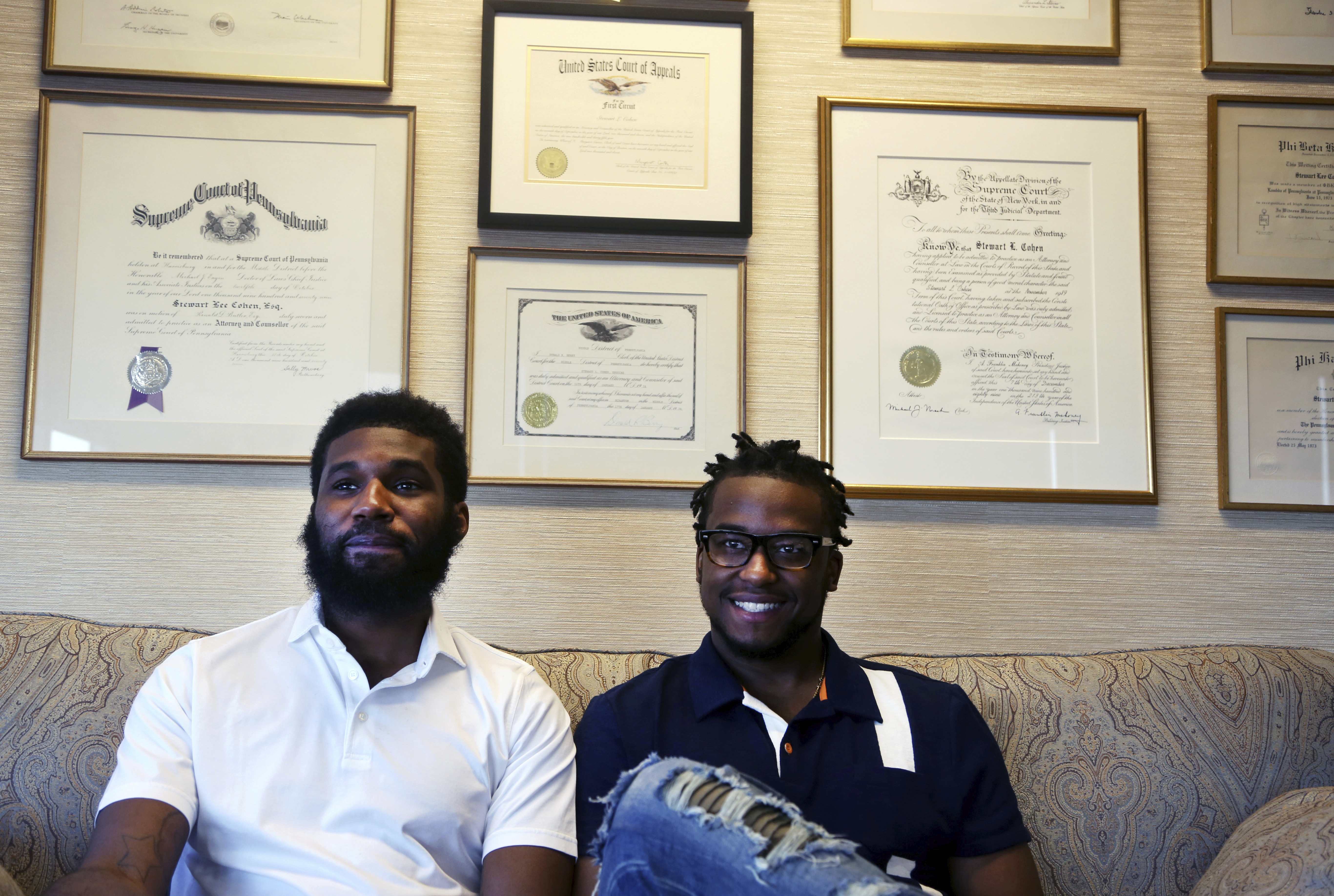 In this Wednesday April 18, 2018 photo, Rashon Nelson, left, and Donte Robinson, right, sit on their attorney's sofa as they pose for a portrait following an interview with The Associated Press in Philadelphia. Their arrests at a local Starbucks quickly became a viral video and galvanized people around the country who saw the incident as modern-day racism.