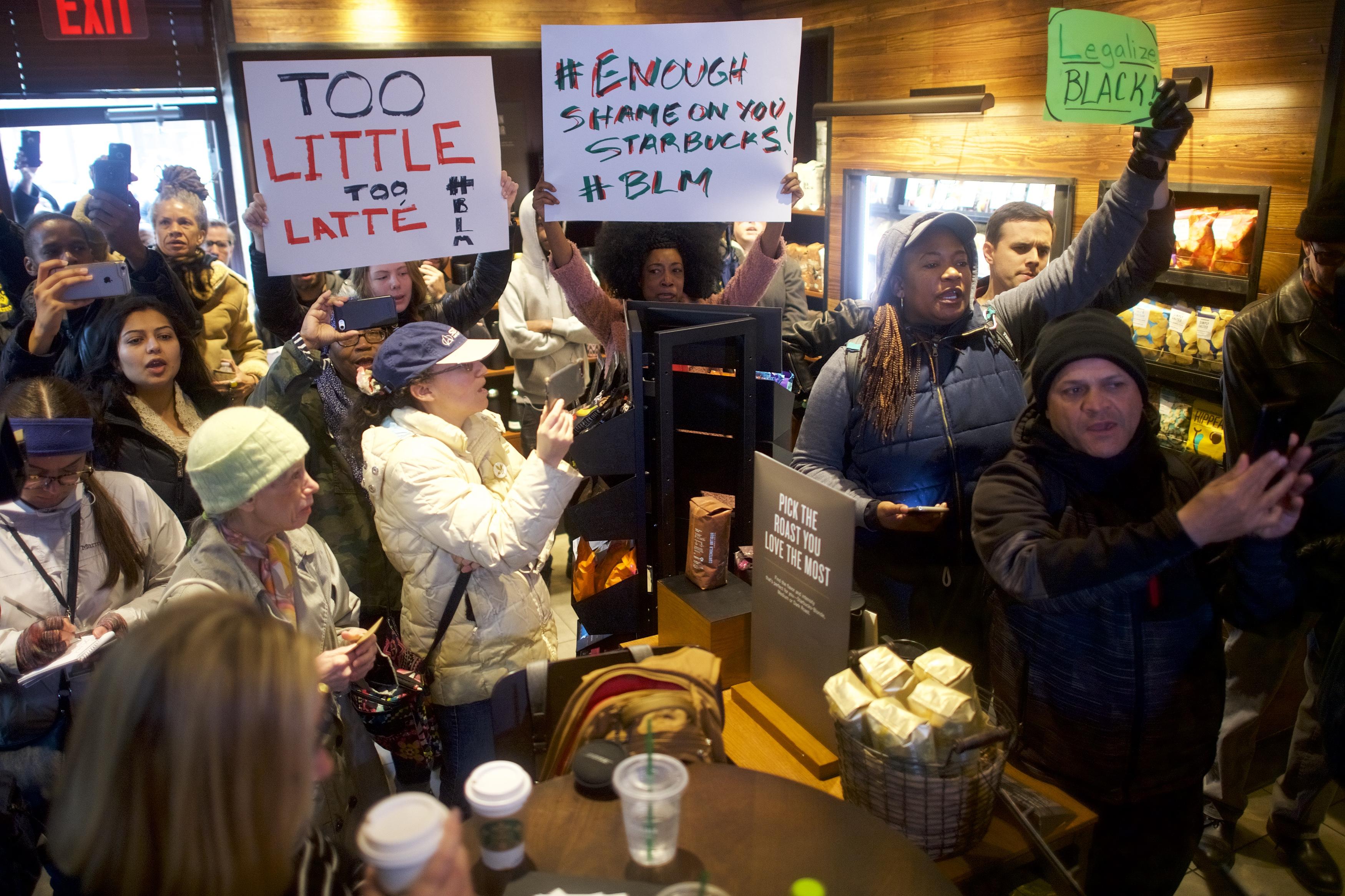 Protestor Donn T (C) demonstrates inside a Center City Starbucks on April 15, 2018 in Philadelphia, Pennsylvania.
