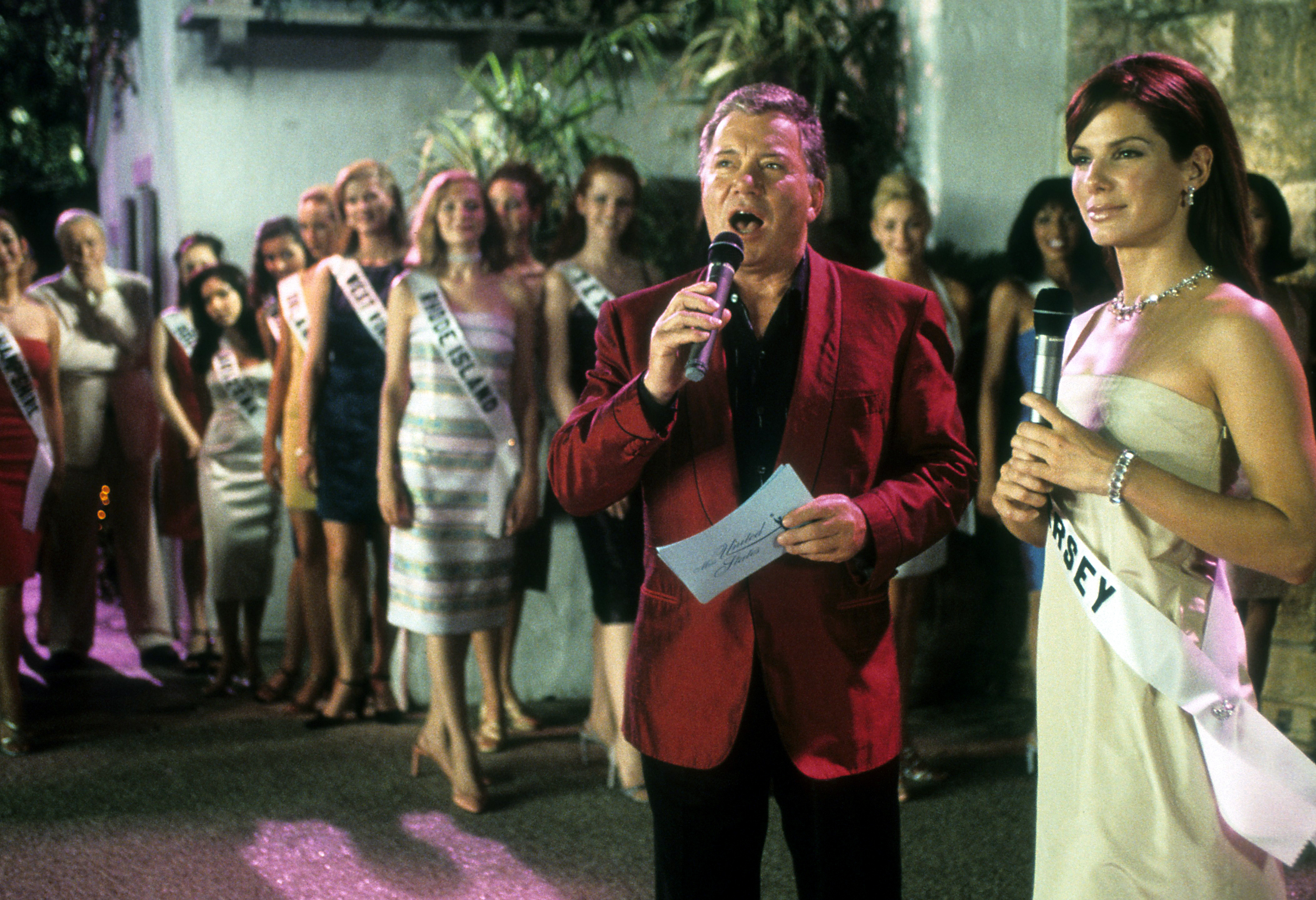 William Shatner speaks into a microphone next to Sandra Bullock in a scene from the film 'Miss Congeniality', 2000. (Photo by Warner Brothers/Getty Images)