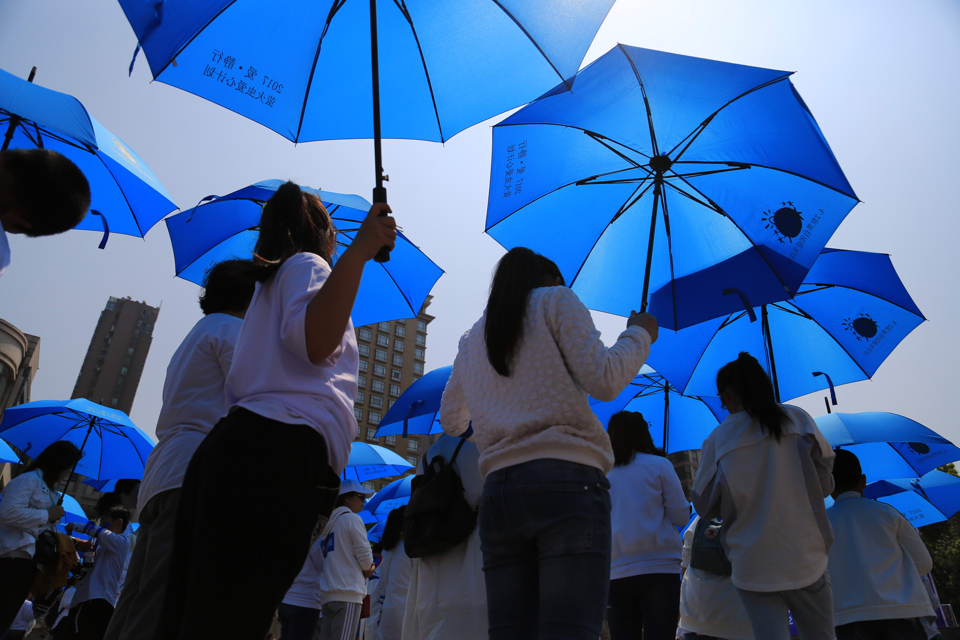 Volunteers holding blue umbrellas walk for 5 kilometers with no speaking on the World Autism Awareness Day at Pujiang County on April 2, 2017 in Jinhua, Zhejiang Province of China.