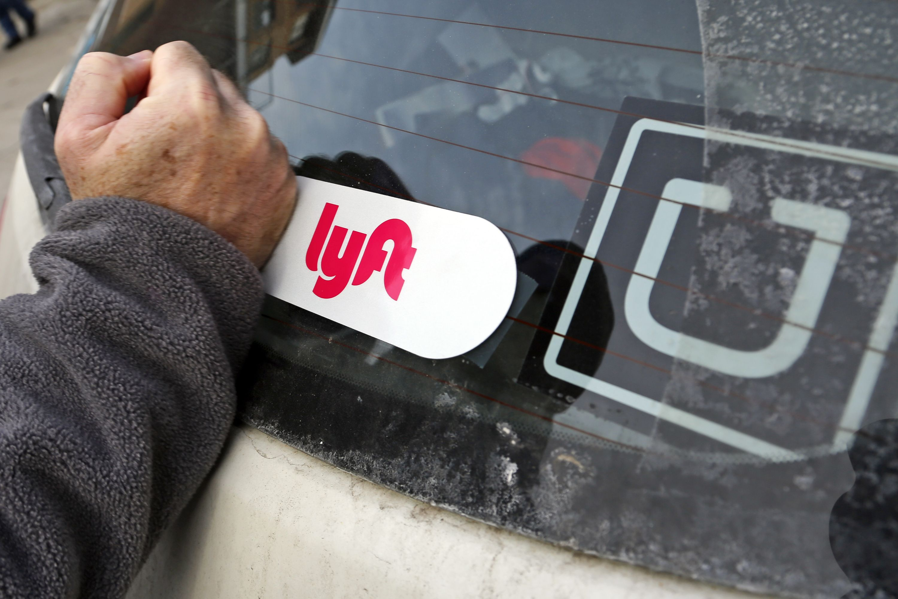 This is a Lyft logo being installed on a Lyft driver's car who also drives for Uber on in Pittsburgh, January 31, 2018.