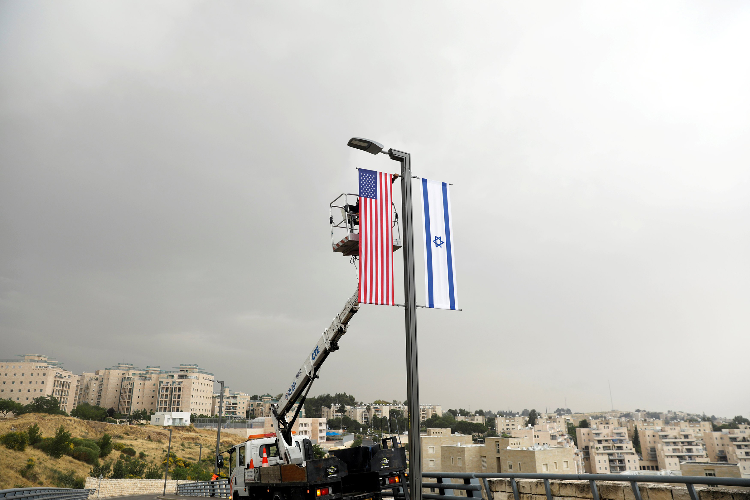 A worker on a crane hangs a U.S. flag alongside an Israeli flag, next to the entrance to the U.S. consulate in Jerusalem, on May 7, 2018.
