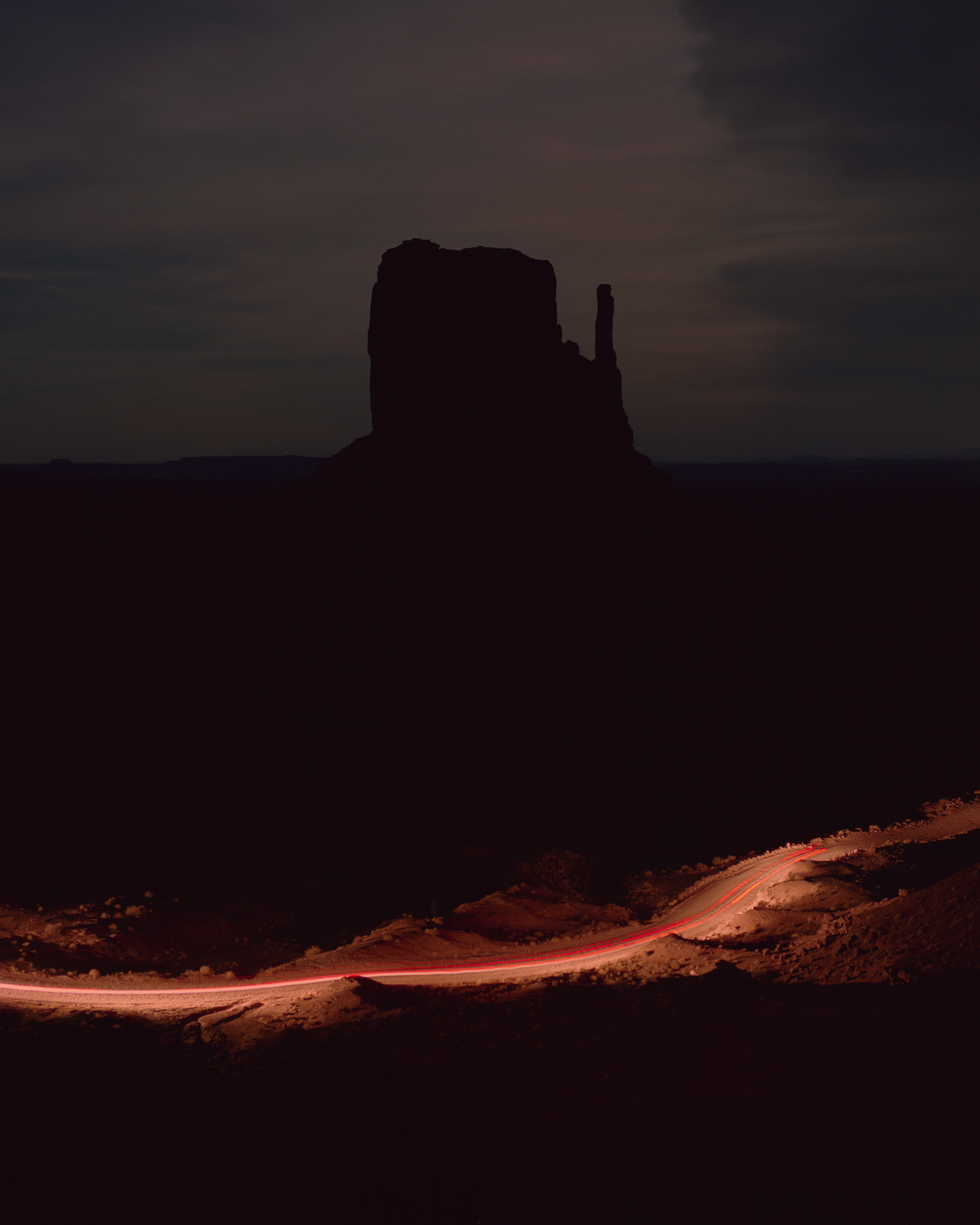 A car illuminates a dirt roadway leading into Monument Valley.