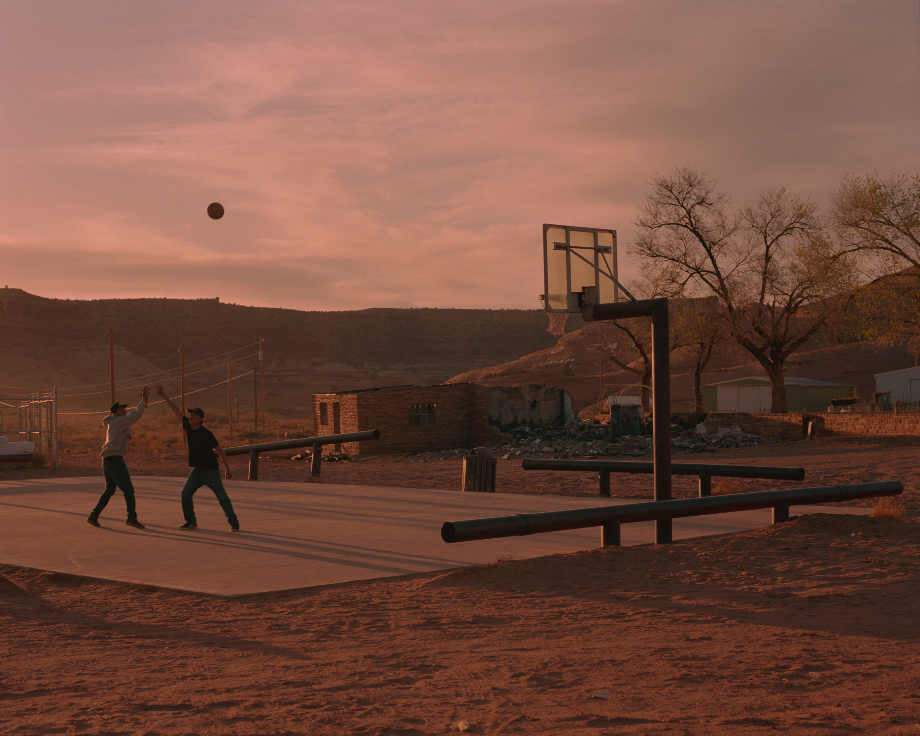 Teenage brothers Deion Salazar and Syrus Yazzieplay basketball in Oljato, Utah - a few miles from Monument Valley. Oljato was a major source for uranium mining in the 1940's and 50's causing serious health concerns for many of its residents.