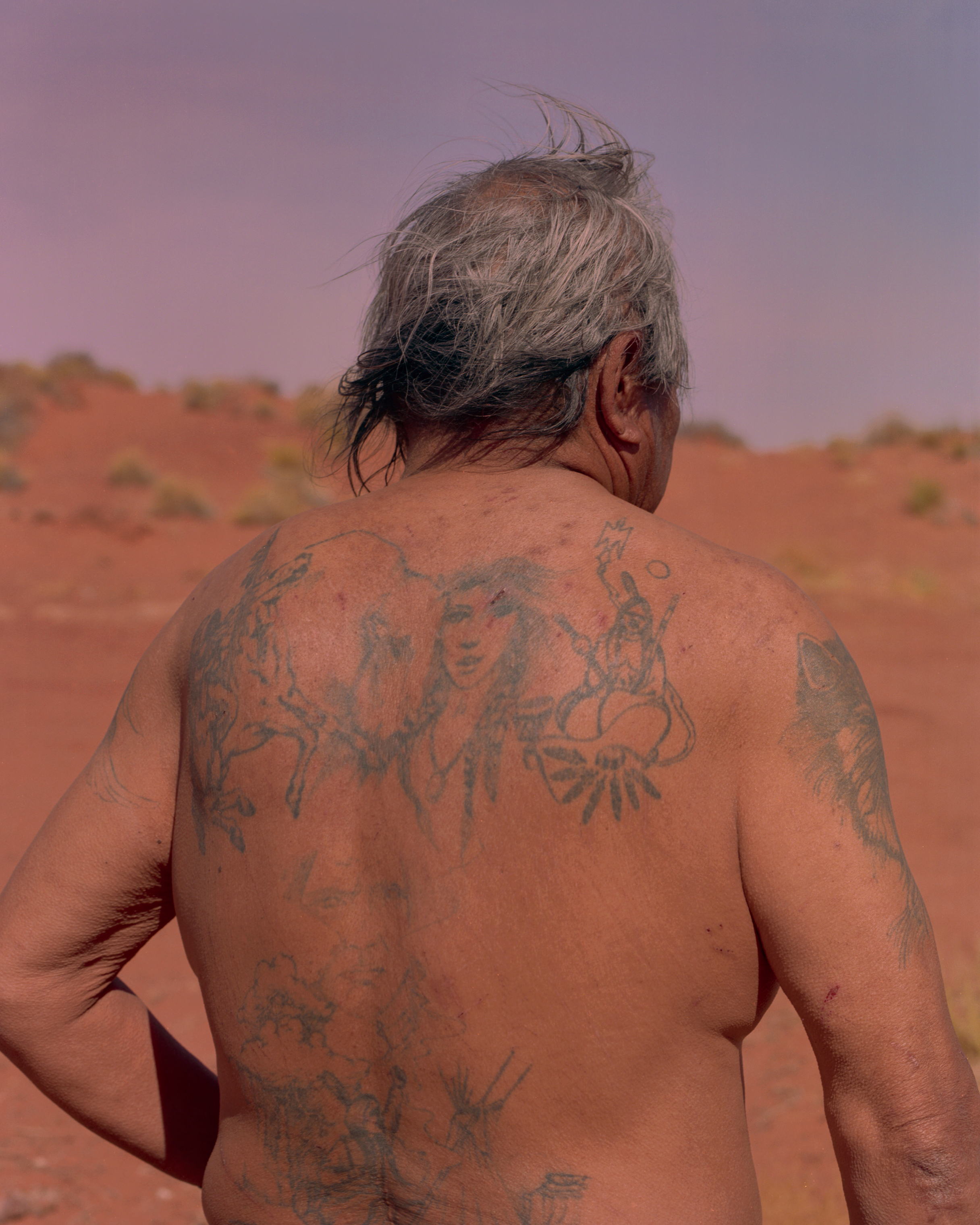 Wilson Collins is pictured at his home in Monument Valley. The tattoos covering his body include traditional Navajo imagery. Collins struggles with alcoholism, a common problem on reservations that is now being addressed by many tribes. He lives in a trailer and spends most of his days with his younger brother, who sells Navajo arts and crafts.