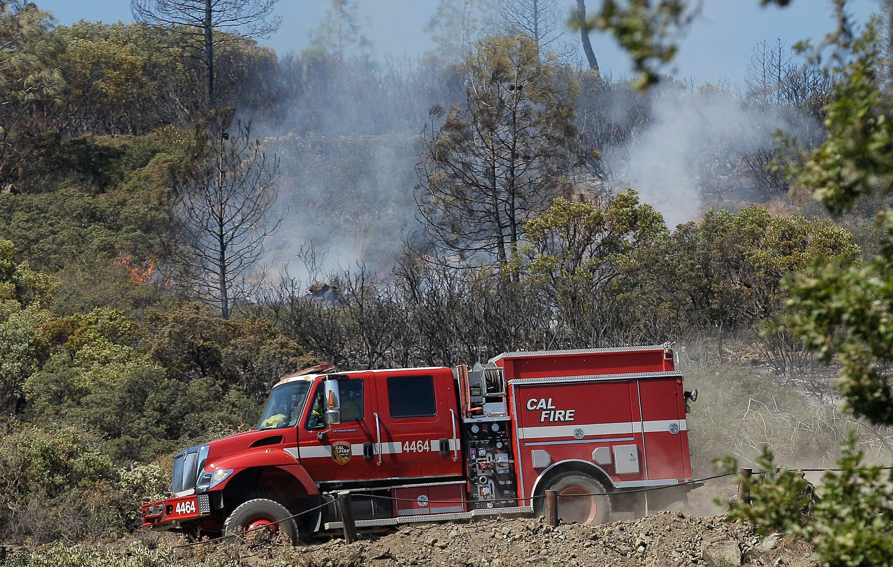 A Cal Fire truck drives down a hill after checking a hot spot near Lower Lake, Calif.