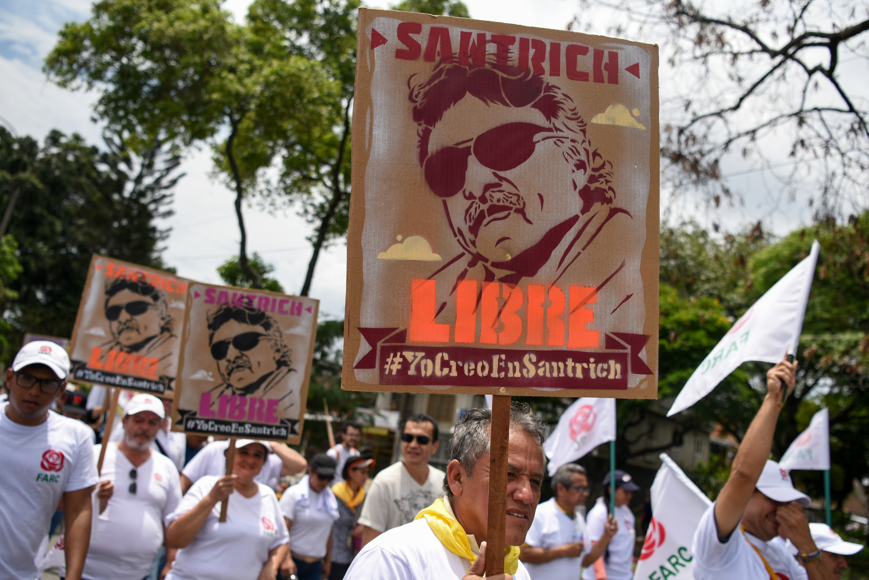 Supporters of the rebel-group-turned-political-party (FARC) hold signs depicting former commander who had been slated to take a seat in Colombia's Congress Jesus Santrich, during a May Day march in Cali, Colombia on May 1, 2018.