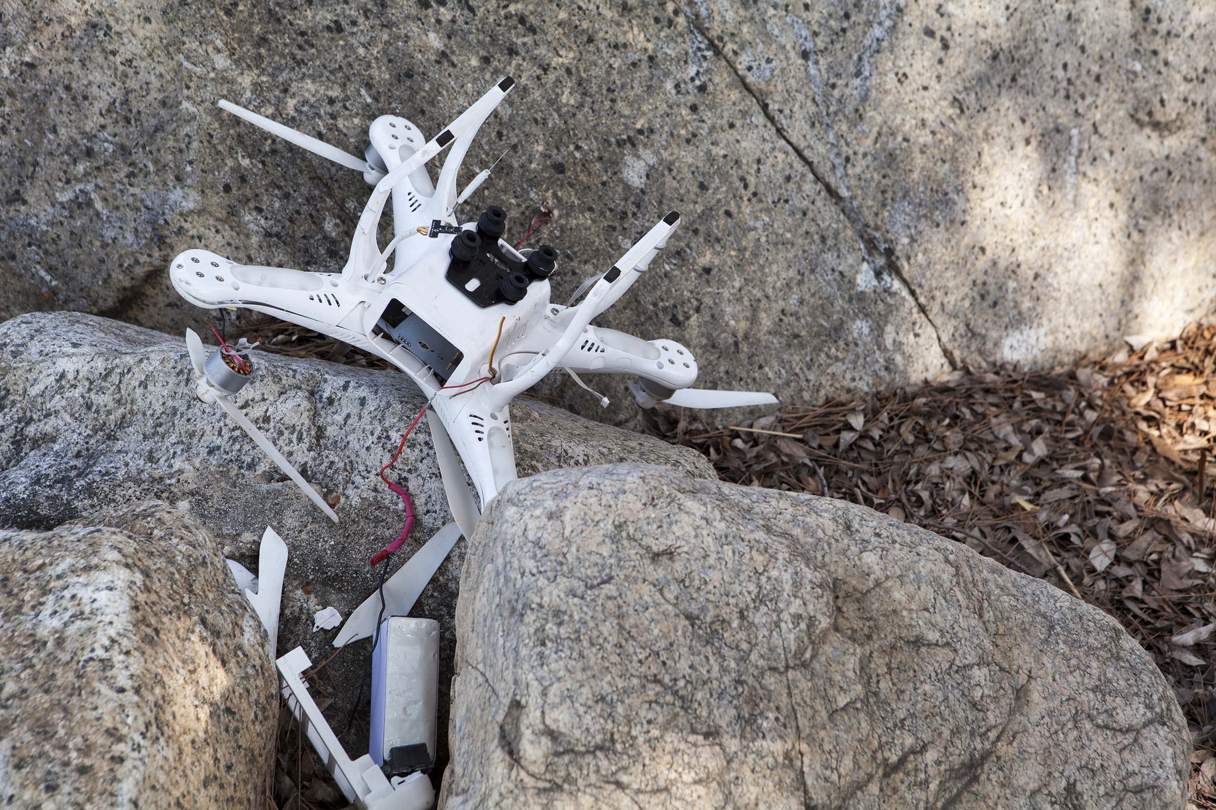 Crashed drone is broken and wedged among rocks with pieces scattered nearby in Altadena, California on August 21, 2016