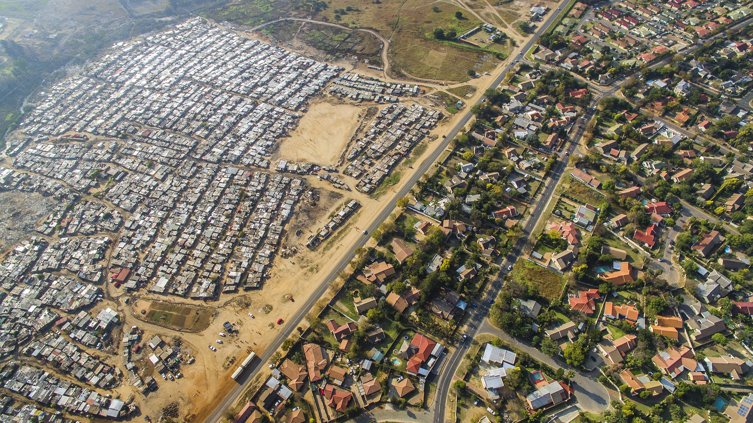 Inequality is found around the globe, but the World Bank says South Africa qualifies as the starkest example. For a vivid perspective on it, Johnny Miller of the Unequal Scenes Project sent a drone over northwest Johannesburg. On the left is Kya Sands, a shack city that is home to many economic migrants who arrived from other African nations. Across the road is Bloubusrand, a middle-class suburb known for its diverse mix of residents.