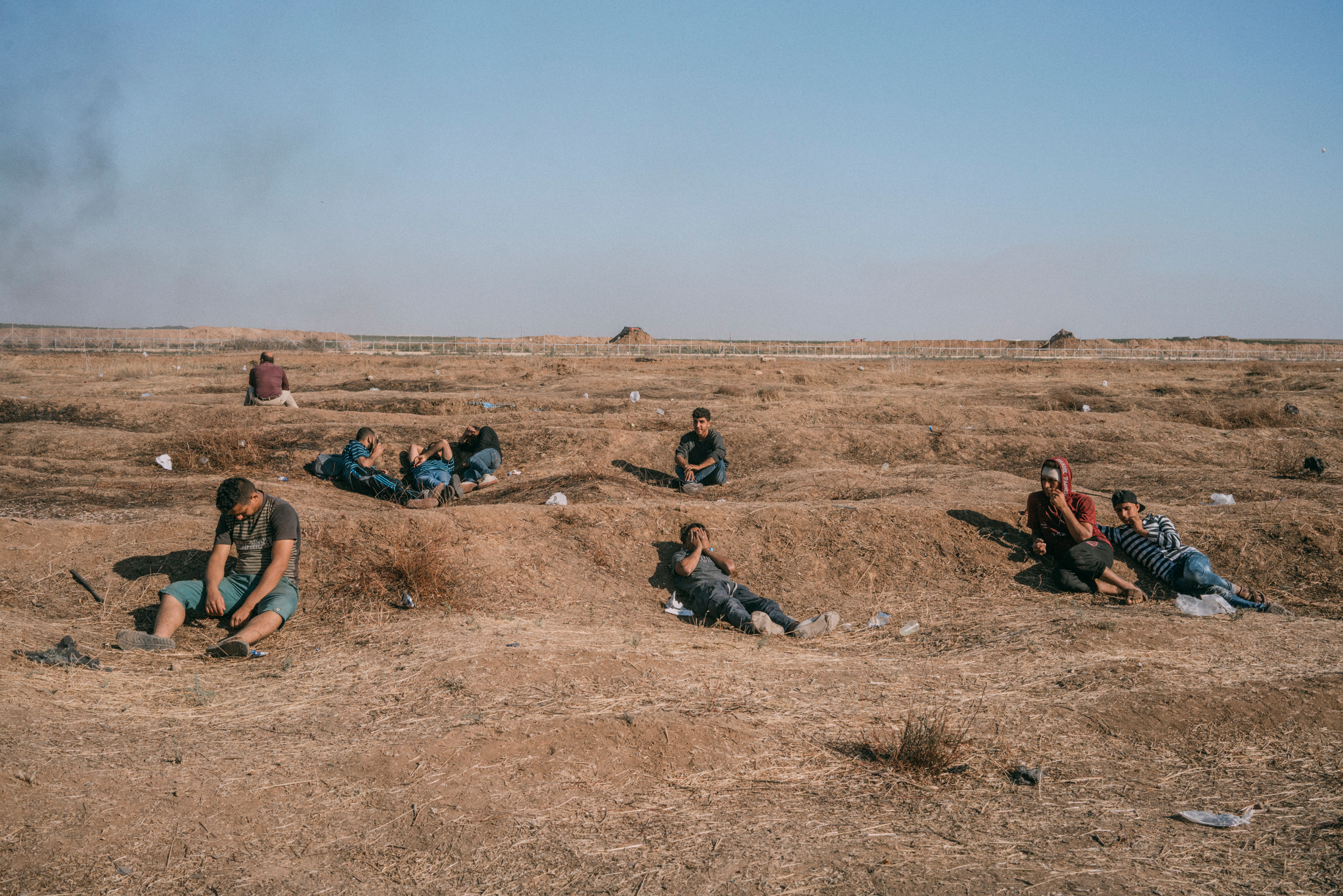 Palestinians sit along the Gaza-Israel border as smoke wafts in the distance.