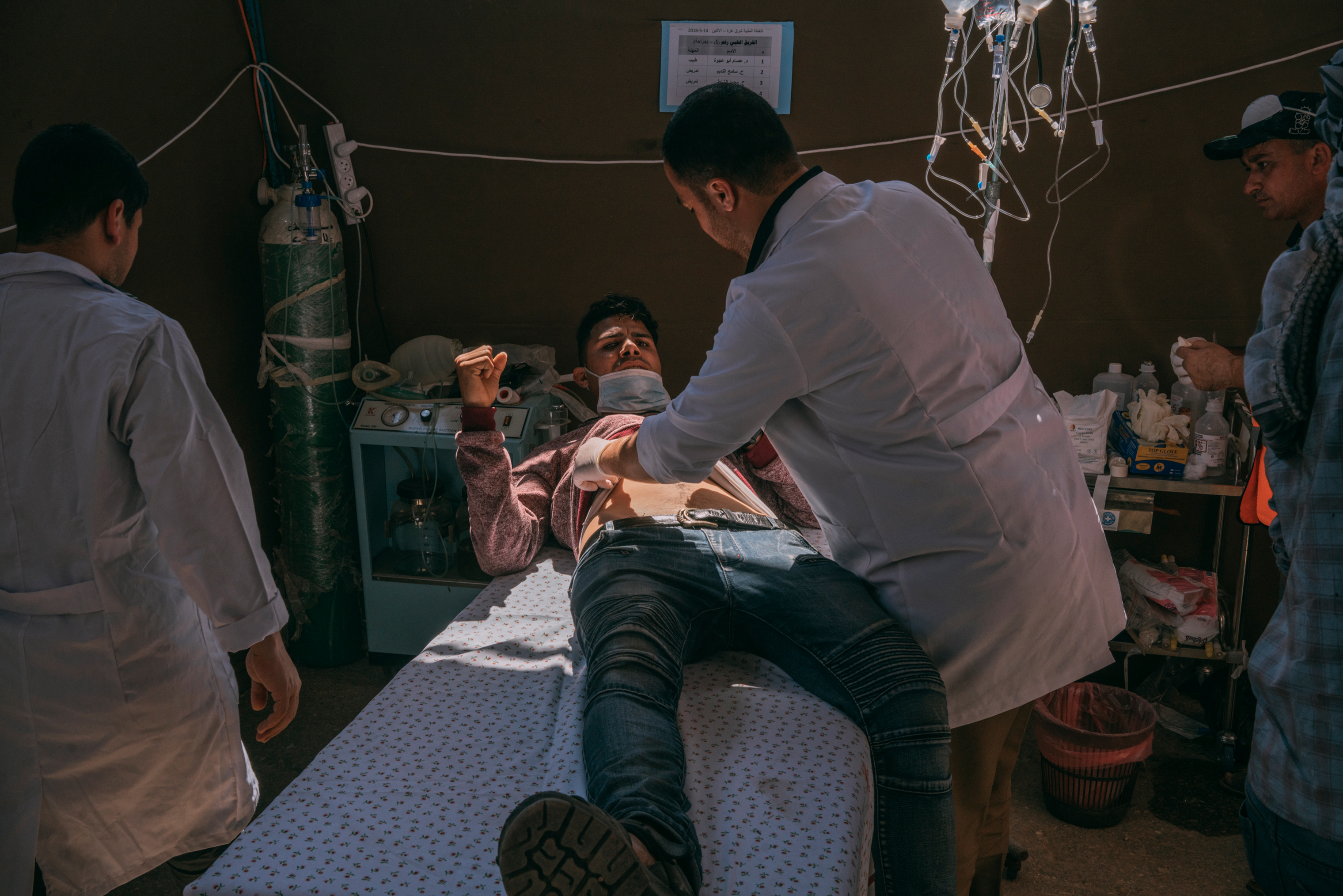 An injured man is assisted by medics in a field hospital set up along the Gaza-Israel border.
