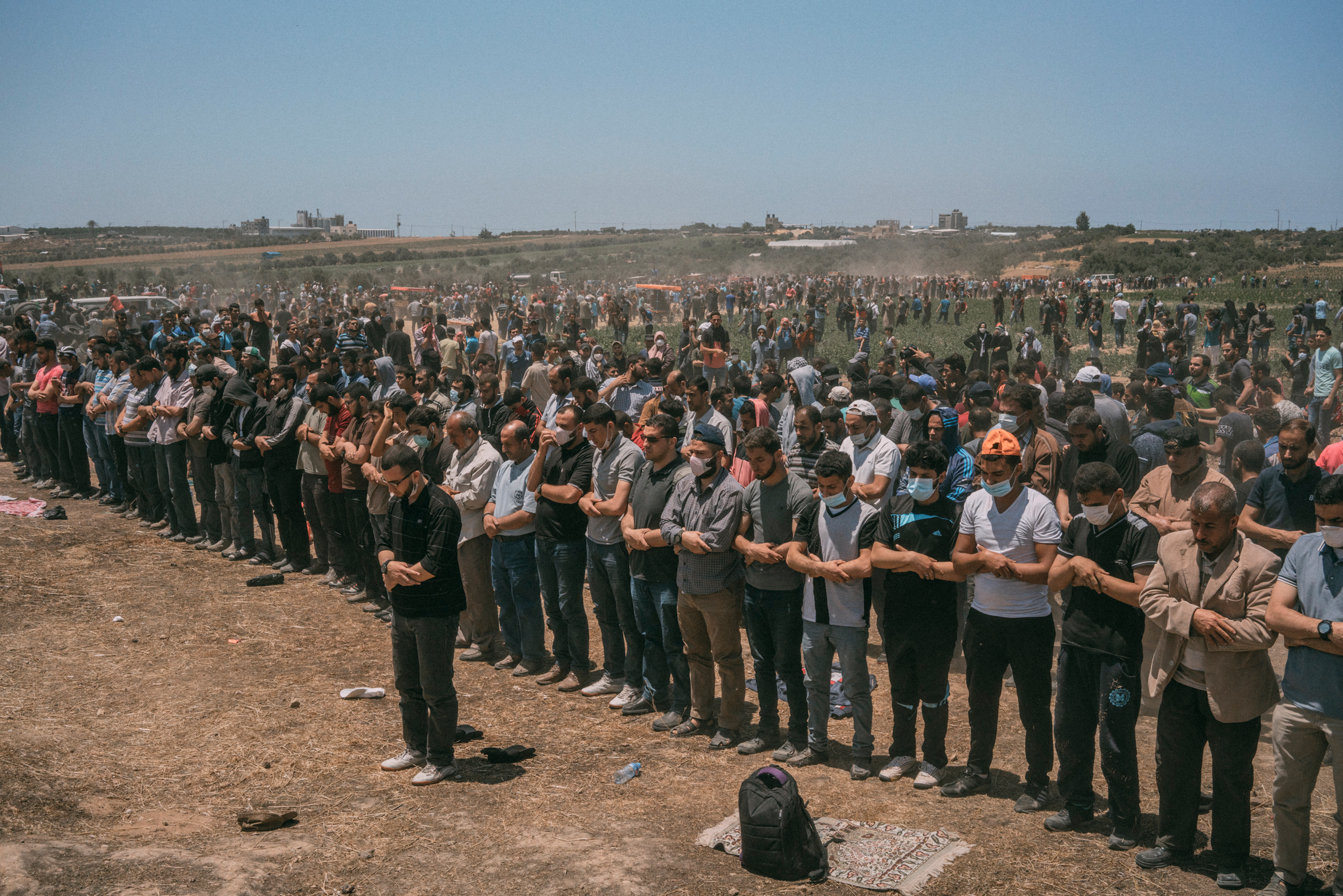 Palestinian men pray along the Gaza-Israel border.