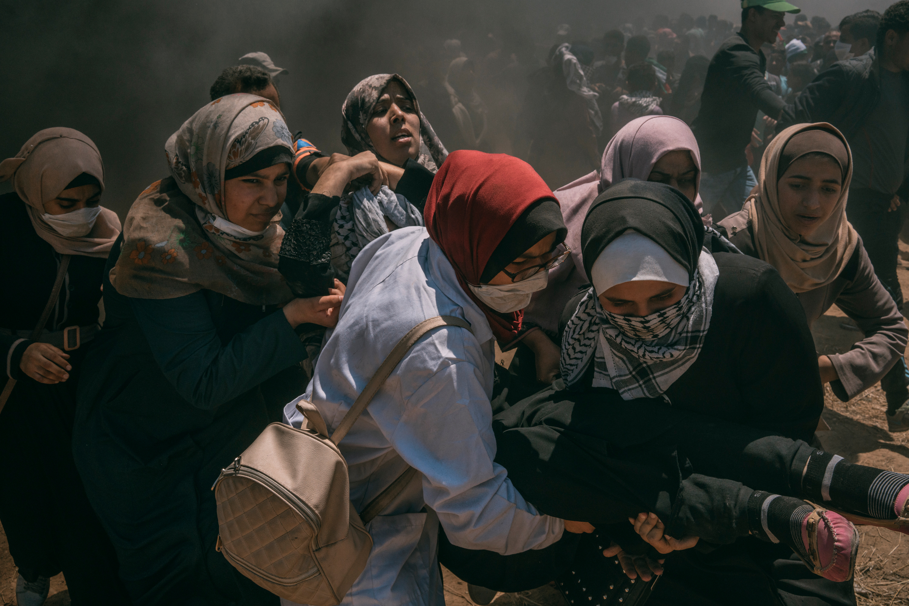 A wounded woman is evacuated by other women after she was injured in the head during the protest along the Gaza-Israel border.