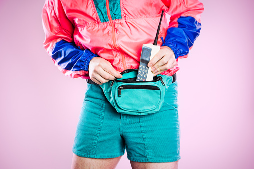 A man wearing fluorescent colored clothing puts a cellular brick phone into his fanny pack