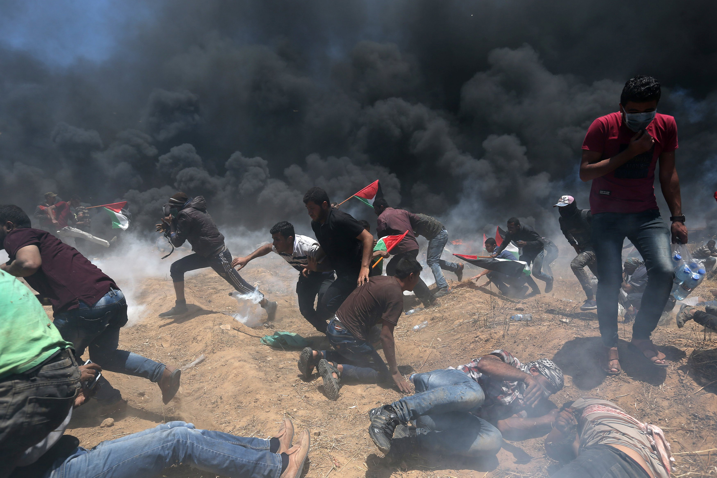 Palestinians run for cover from Israeli fire and tear gas during a protest against the relocation of the U.S. embassy to Jerusalem, at the Israel-Gaza border in the southern Gaza Strip, on May 14, 2018.