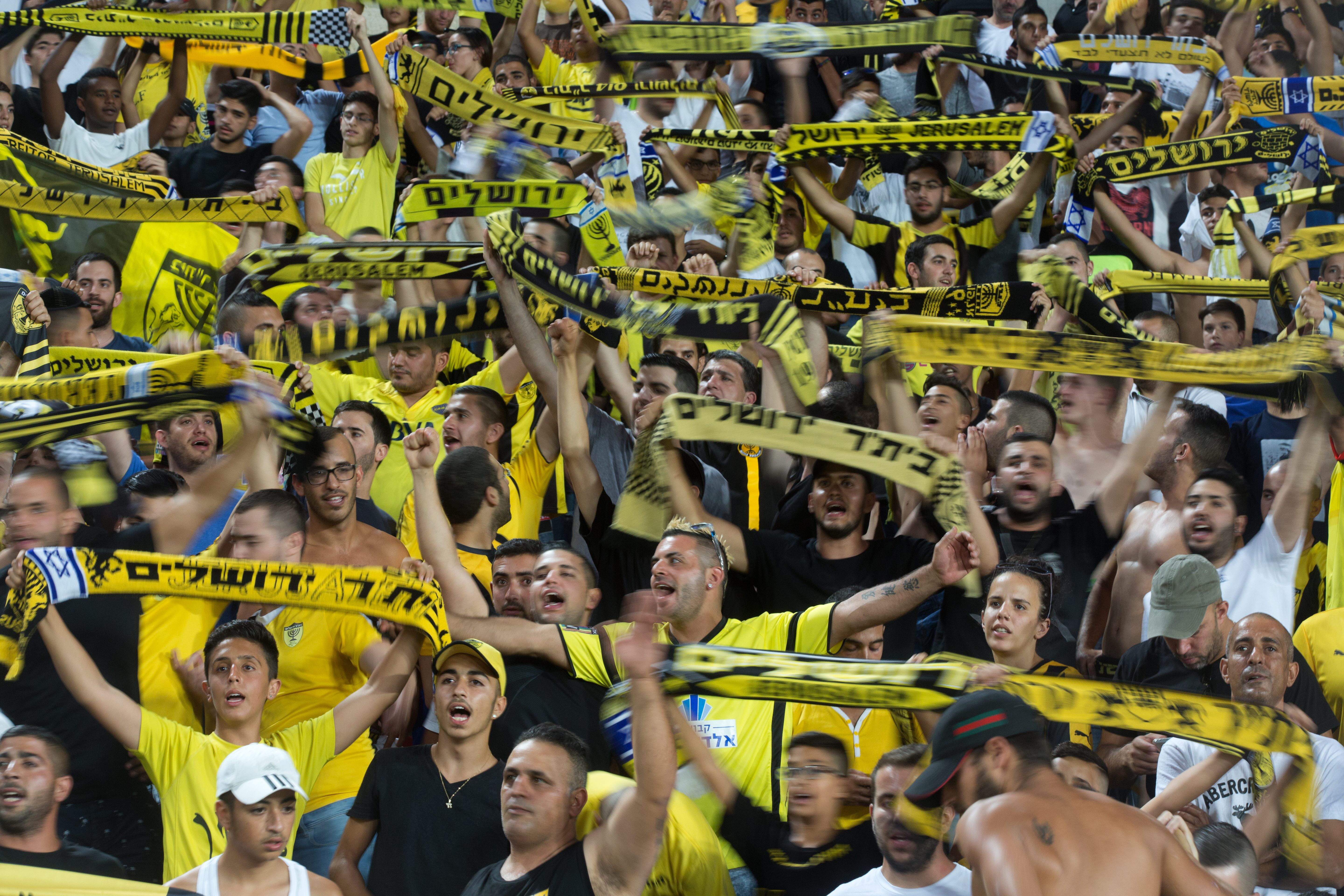 Supporters of Israeli football club Beitar Jerusalem cheer during their clubs return match against Belgium team Charleroi on July 23, 2015 at Teddy Stadium in Jerusalem.