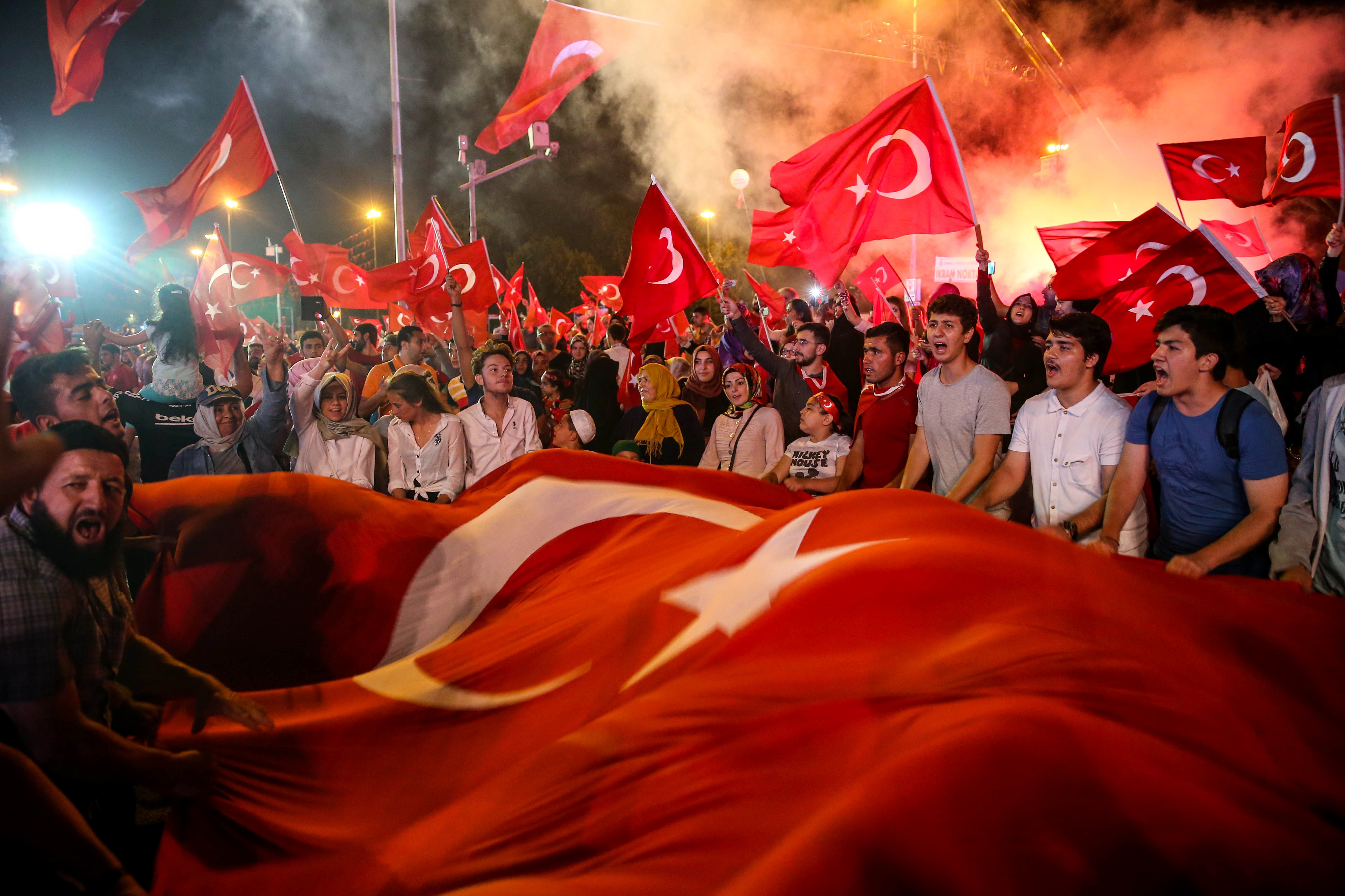 People wave a giant Turkish flag during a protest against a failed military coup attempt in Istanbul, Turkey on July 29, 2016.