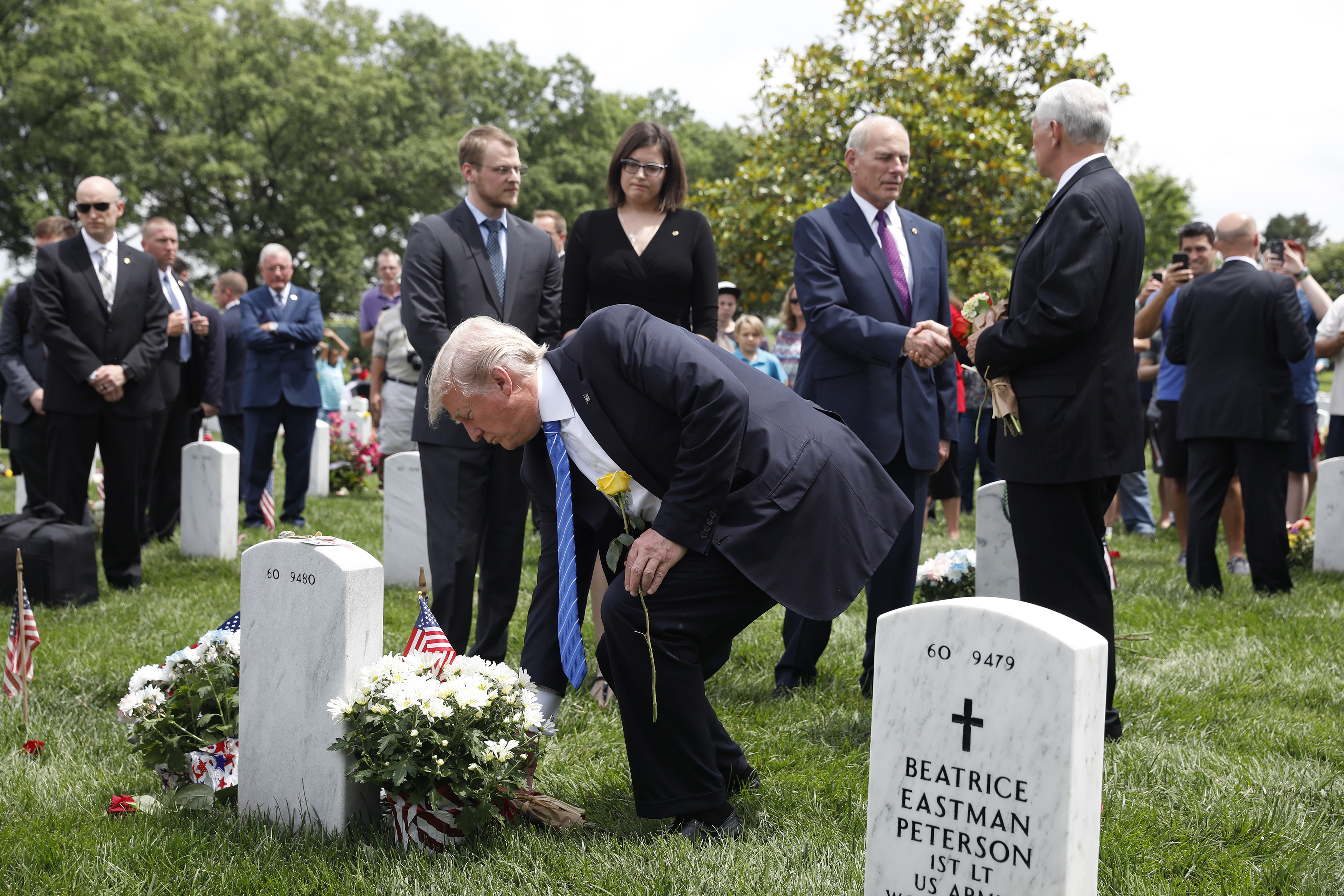As Vice President Mike Pence and White House Chief of Staff John Kelly shake hands, President Donald Trump lays flowers on the grave of Kelly's son Robert at Arlington National Cemetery on May 29, 2017 in Arlington, Virginia. Marine Lieutenant Robert Kelly was killed in 2010 while leading a patrol in Afghanistan