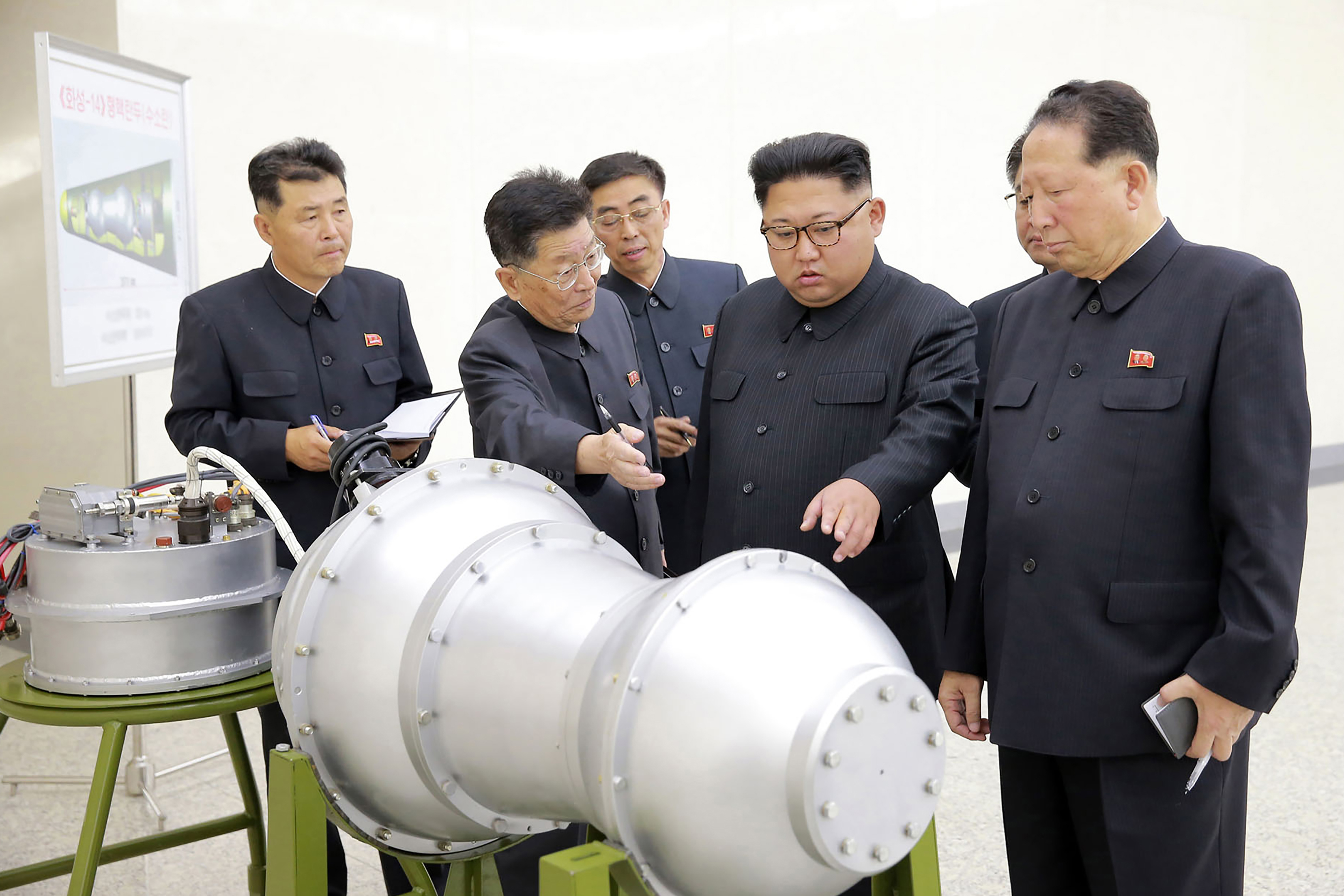 This undated picture released by North Korea's official Korean Central News Agency (KCNA) on September 3, 2017 shows North Korean leader Kim Jong-Un looking at a metal casing with two bulges at an undisclosed location.