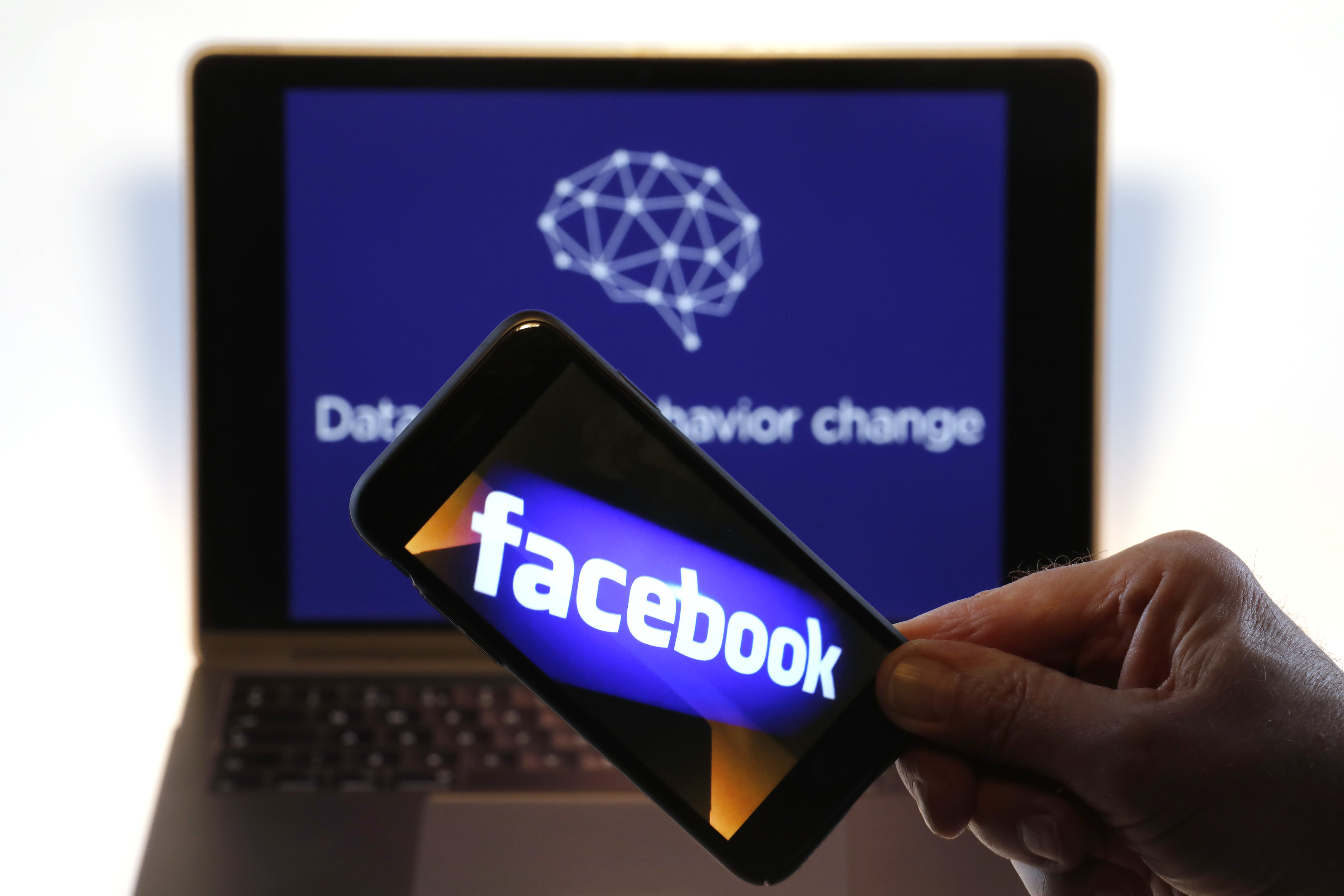 The Facebook Inc. logo is displayed on an Apple Inc. iPhone against the backdrop of the Twitter Inc. banner image from Cambridge Analytica's verified twitter page, displayed on a computer screen in this arranged photograph in London, U.K., on Thursday, March 22, 2018.