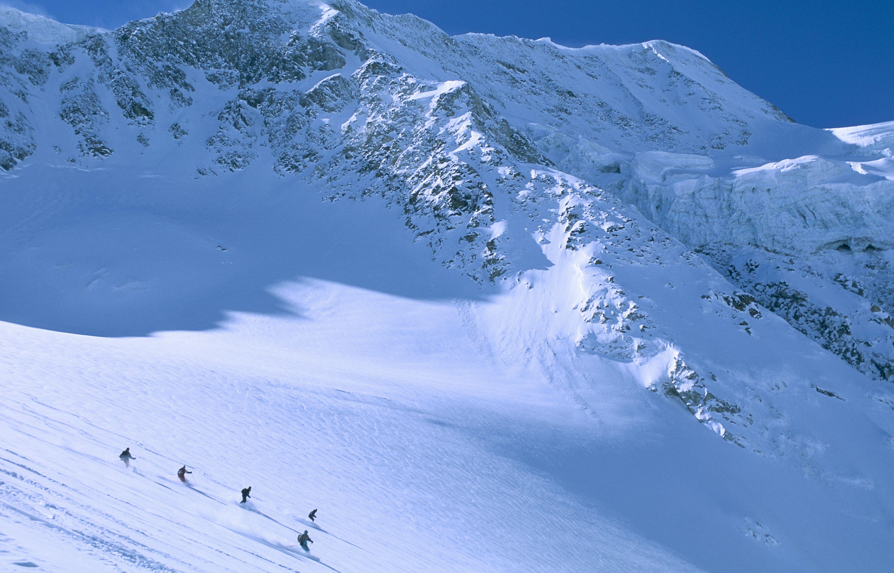 Skiers descend Pigne D'Arolla near Arolla, Switzerland.