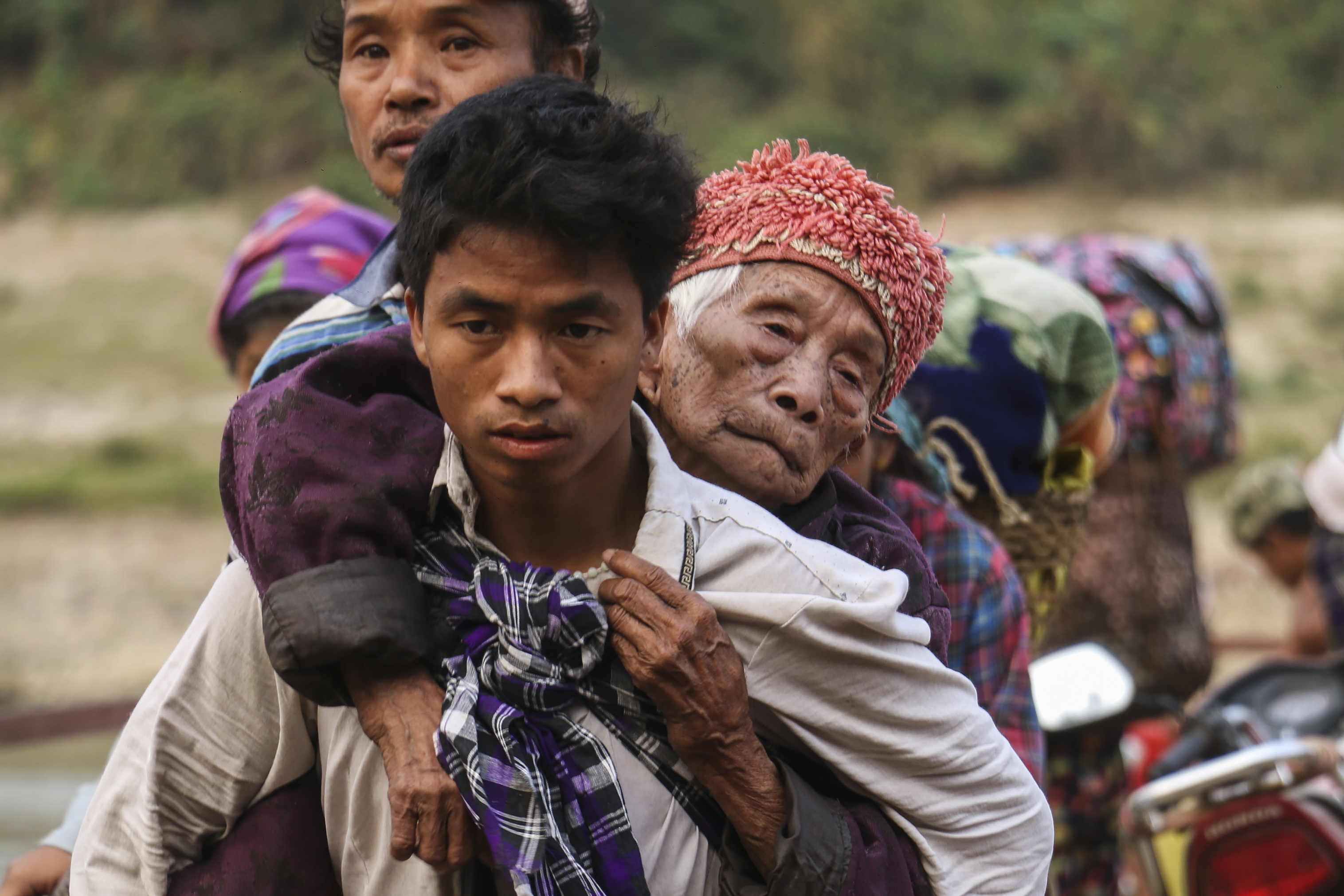 This picture taken on April 26, 2018 shows displaced Kachin residents crossing Malikha river to escape the fighting in Injanyan village near Myitkyina, Myanmar's Kachin state.