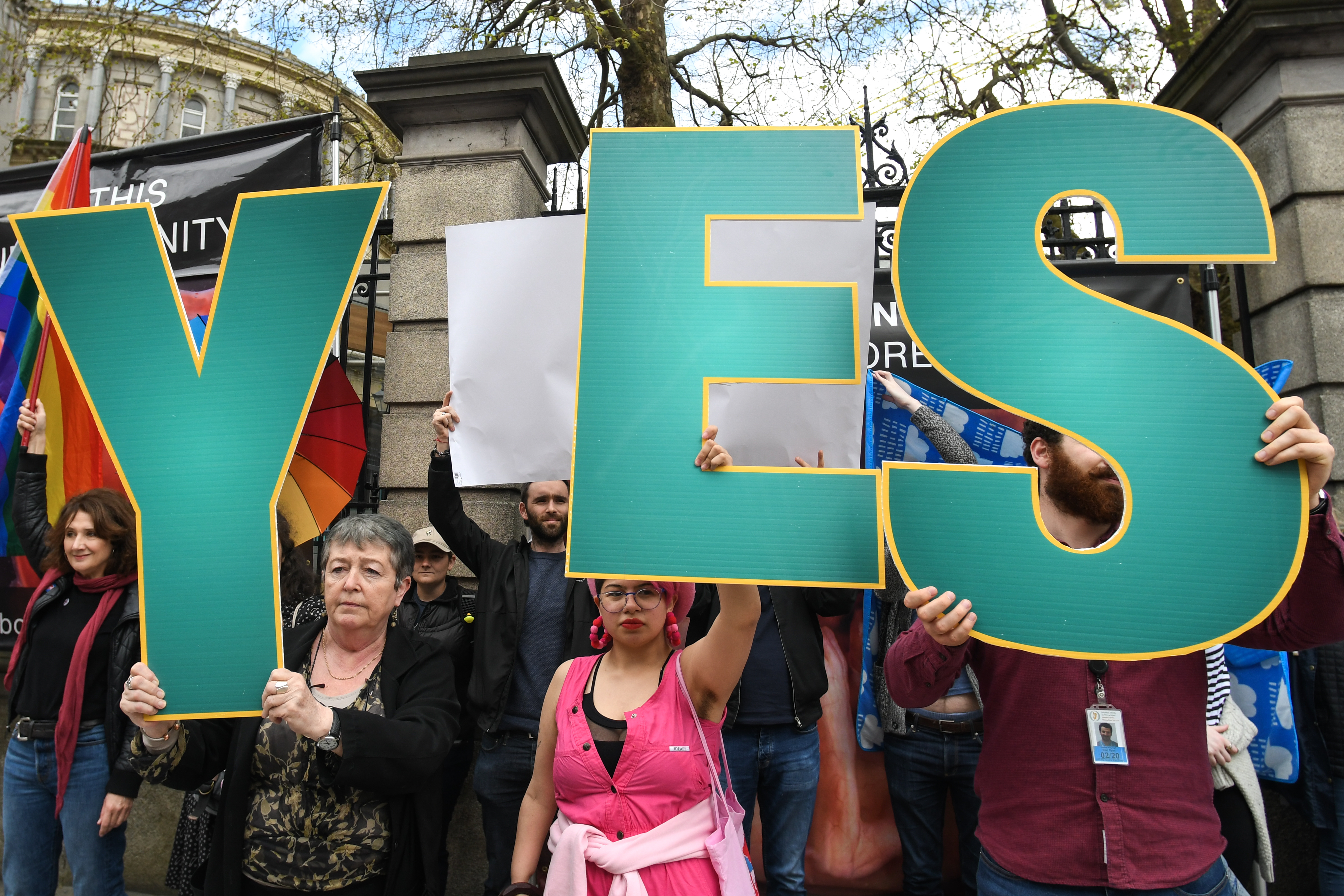'Yes' vote campaigners cover anti-abortion group's graphic images related to pregnancy and abortion, with Irish and rainbow flags, and white billboards, outside Leinster House, the Irish Parliament, on Friday, May 4, 2018, in Dublin, Ireland.