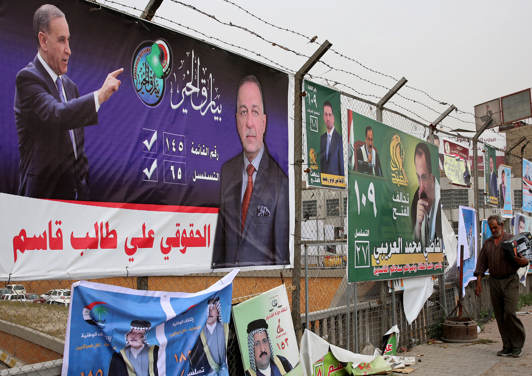 Posters of candidates in Iraq's upcoming parliamentary elections are seen with Arabic slogans in the streets of Baghdad on May 8, 2018.