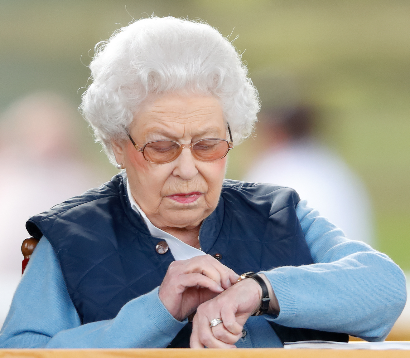 The Queen consults her wristpiece during the event. (Photo by Max Mumby/Indigo/Getty Images