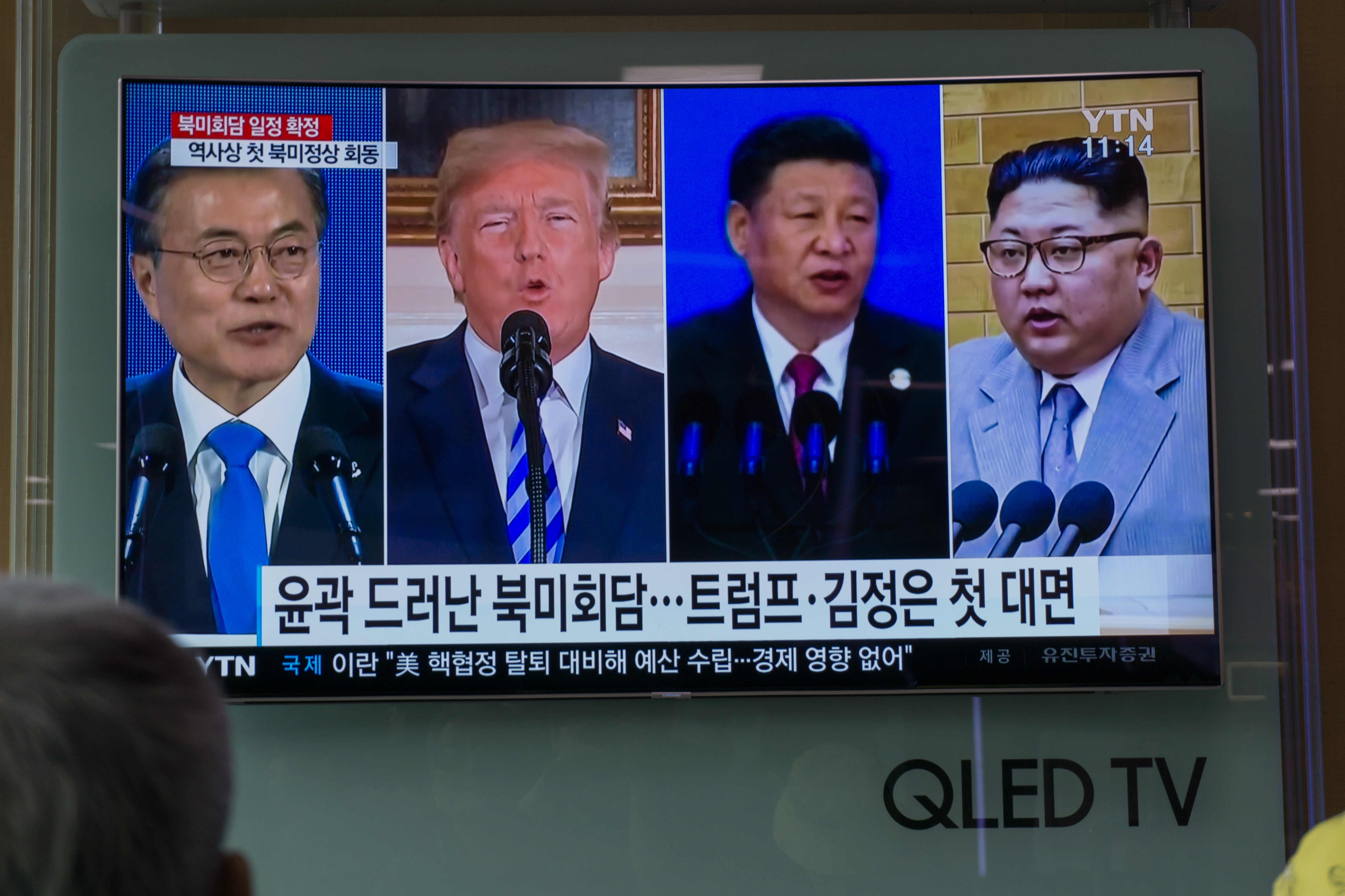 People watch a screen showing images of South Korea's president Moon Jae-in, U.S. president Donald Trump, China's president Xi Jinping, and North Korea's leader Kim Jong Un at a railway station in Seoul on May 11, 2018.