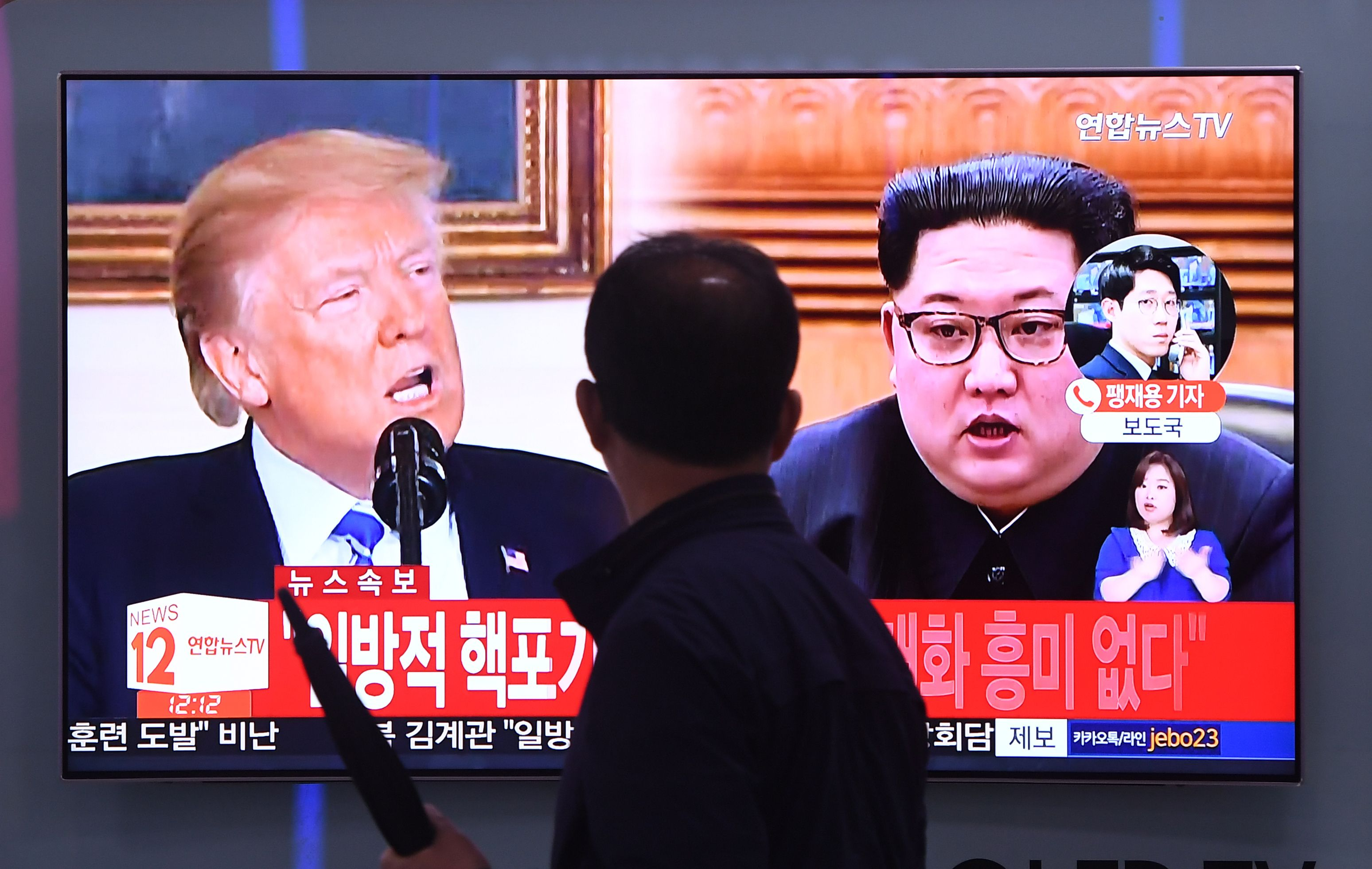 A man walks past a television news screen showing North Korean leader Kim Jong Un (R) and US President Donald Trump (L) at a railway station in Seoul on May 16, 2018.