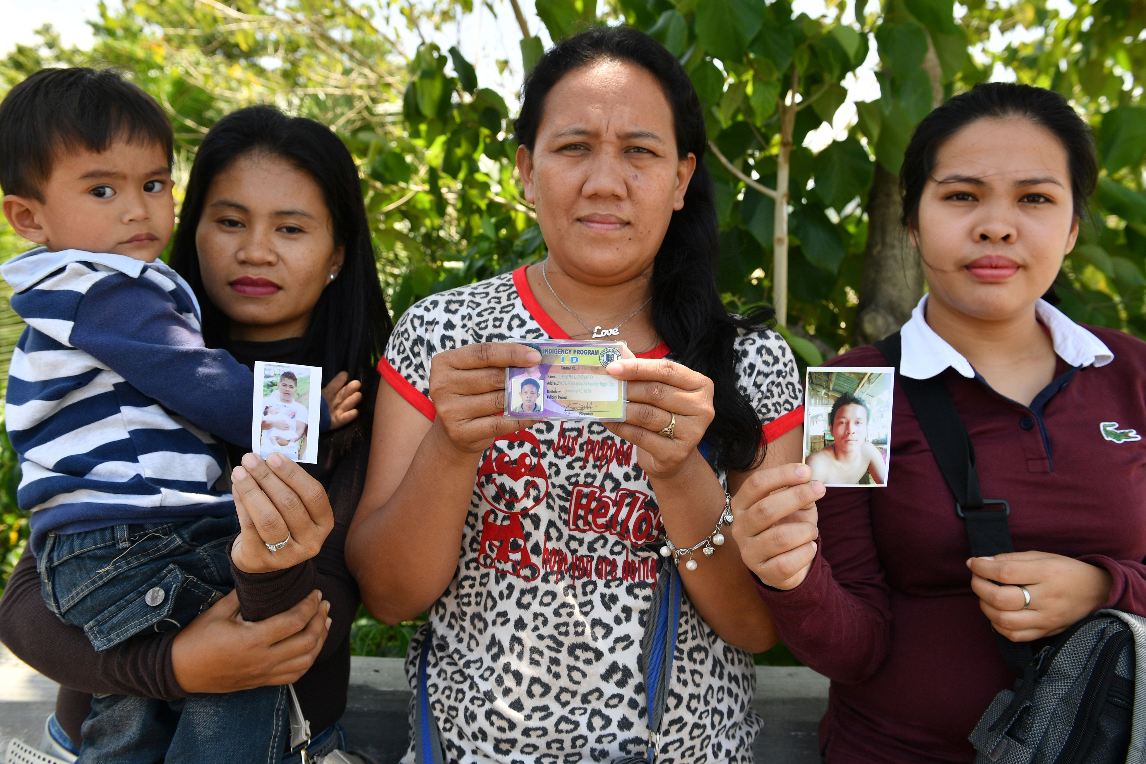Women show photos of their husbands who are still missing one year after the Marawi siege.