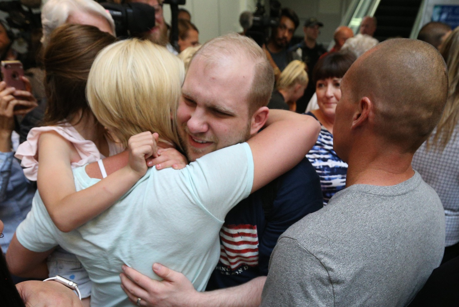 Friends and family hug and greet Josh Holt, upon his return to Utah at the Salt Lake City International Airport on May 28, 2018 in Salt Lake City, Utah.