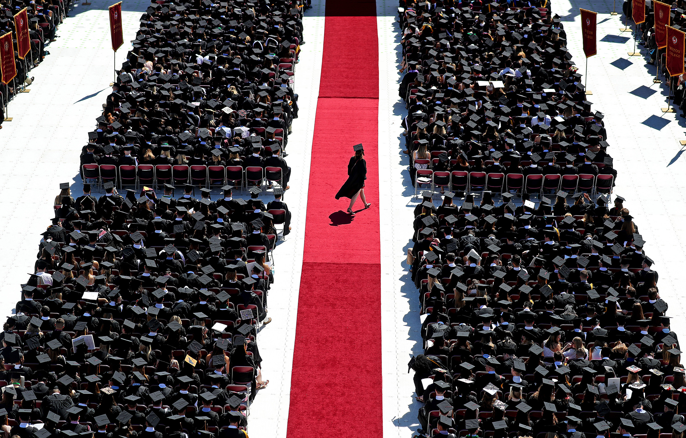 A graduate crosses the red carpet during the Boston College commencement at Alumni Stadium in Boston on May 21, 2018