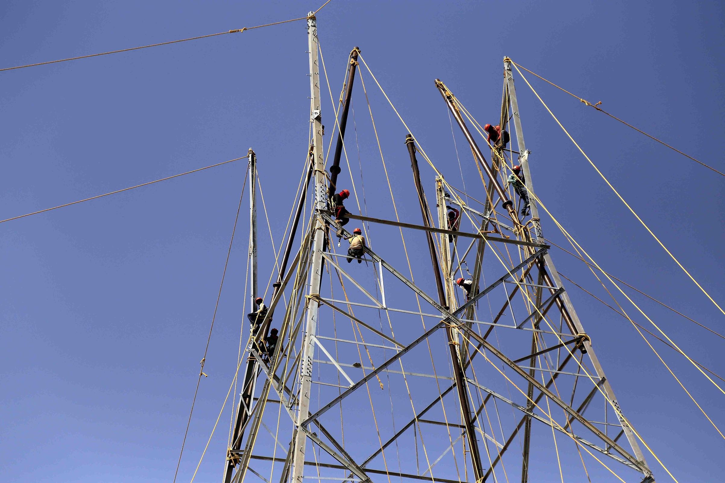 Indian workers install a new electric pole for power lines on the outskirts of Ajmer, in the Indian state of Rajasthan on April 14, 2018