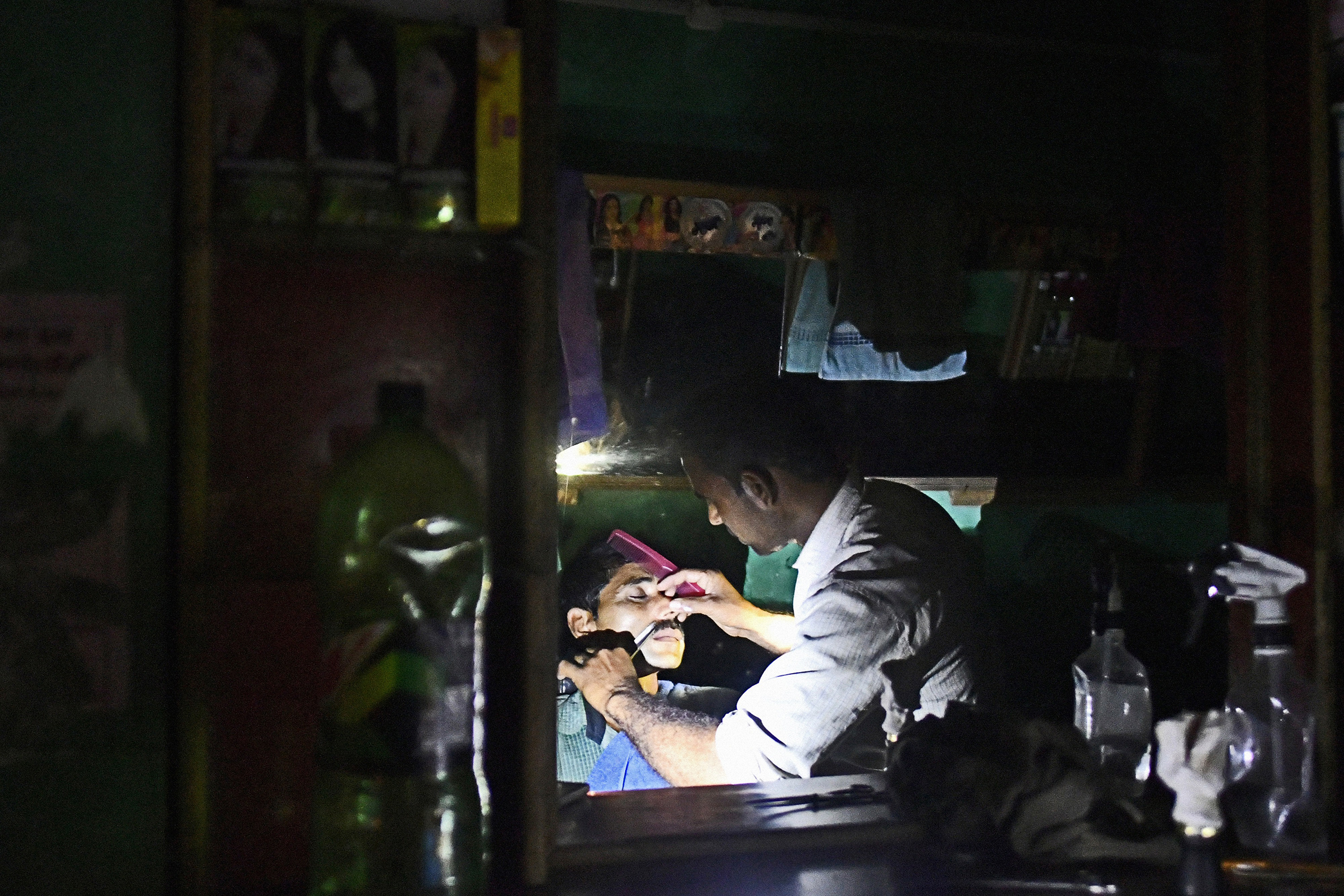 A customer gets a shave at a barber shop illuminated by the torch function of a mobile phone in a village on the outskirts of Alwar, Rajasthan, India on April 17, 2018.