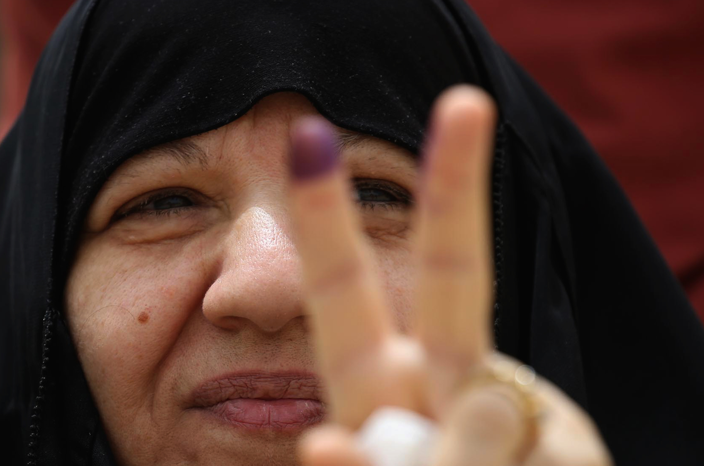 An Iraqi woman voter flashes the victory gesture with her ink-stained index finger at a poll station in the holy city of Karbala on May 12, 2018.