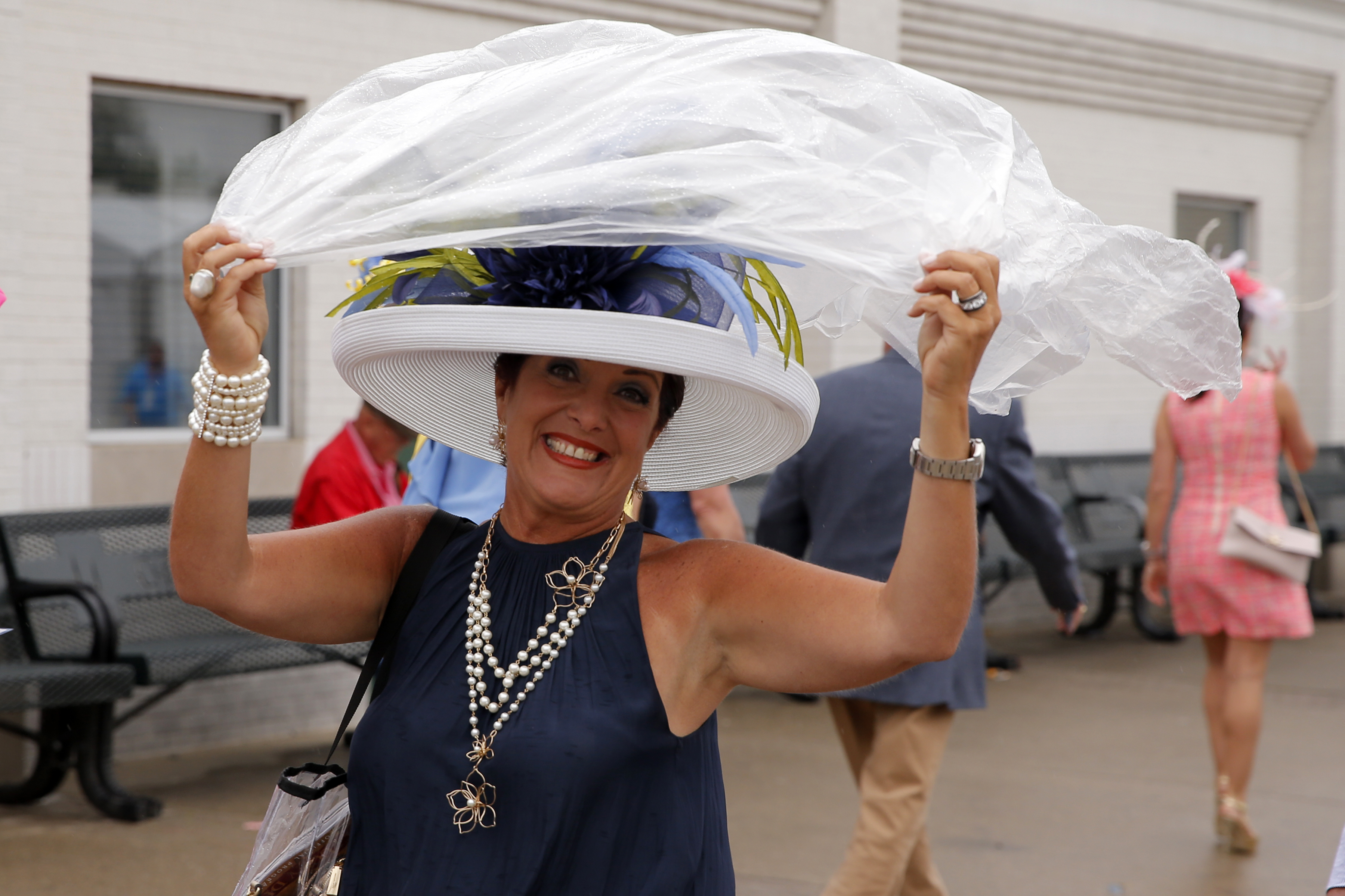 A derby fan tries to protect her hat from the rain during the 144th running of the Kentucky Derby at Churchill Downs on May 5th, 2018 in Louisville, Kentucky.