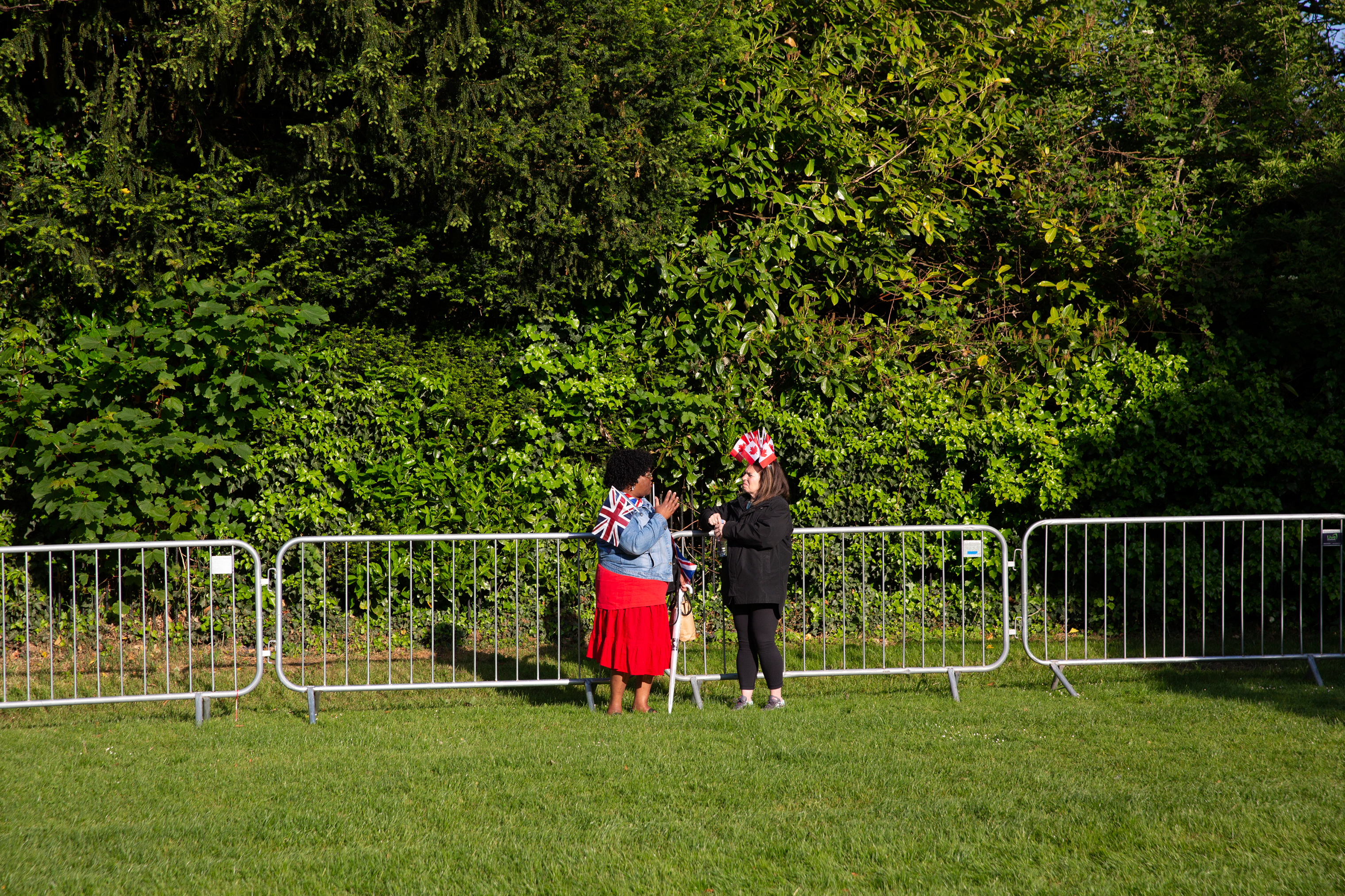 Two women talk away from the crowds of spectators.