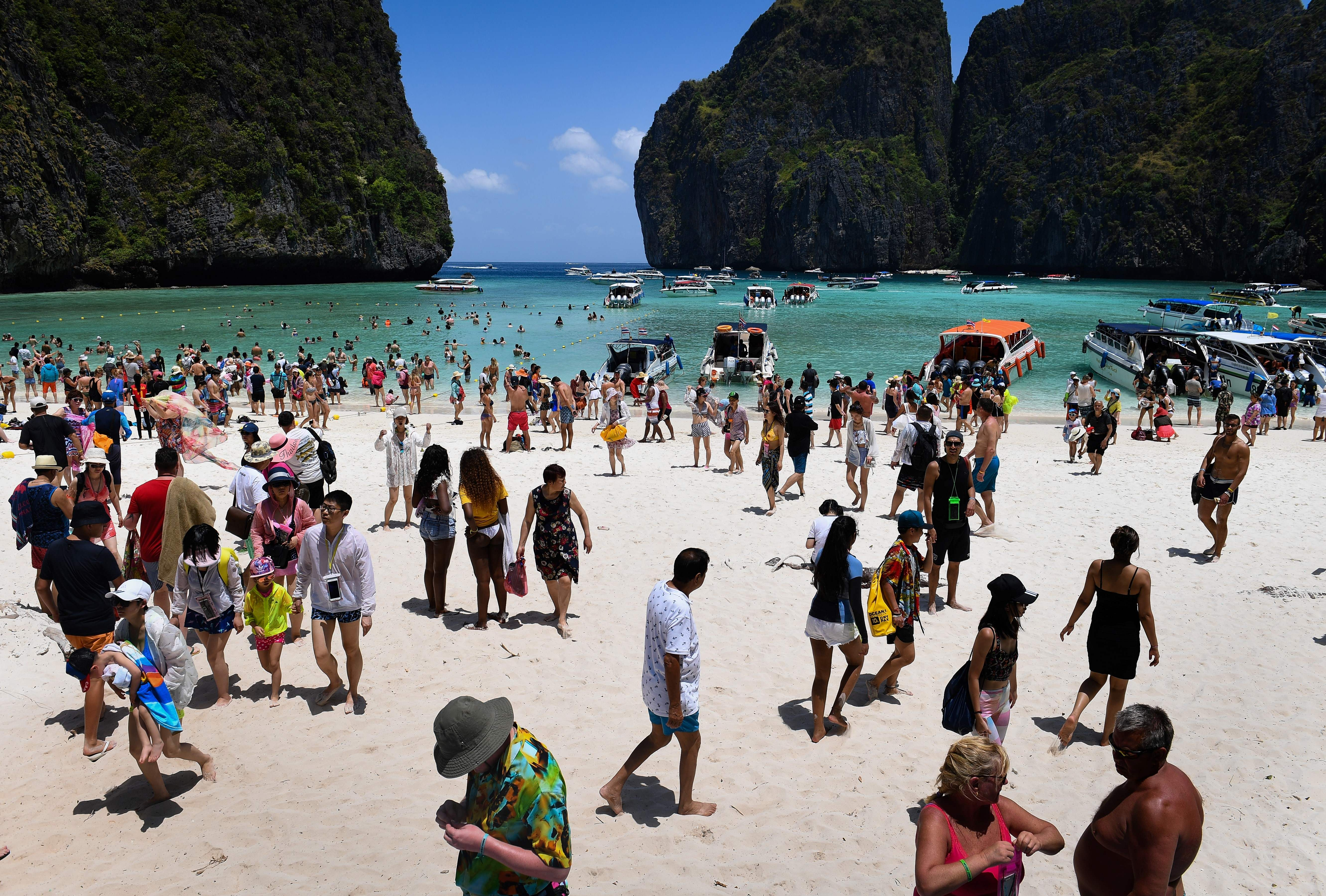 This photo taken on April 9, 2018 shows a crowd of tourists on the Maya Bay beach, on the southern Thai island of Koh Phi Phi.                       Across the region, Southeast Asia's once-pristine beaches are reeling from decades of unchecked tourism as governments scramble to confront trash-filled waters and environmental degradation without puncturing a key economic driver.