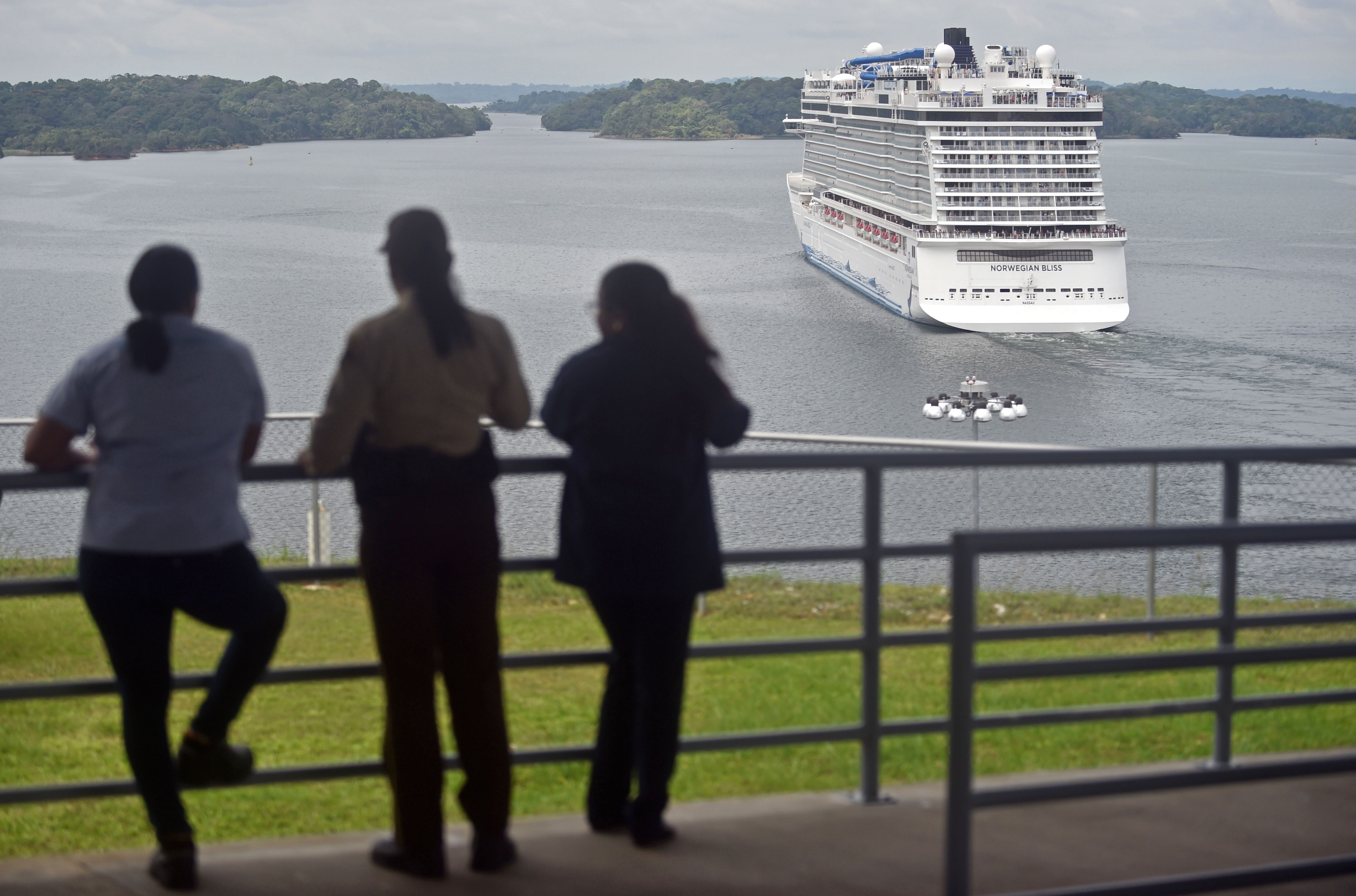 People look at a cruise ship crossing the Panama Canal in the Agua Clara locks in Colon 80 km northwest from Panama City.