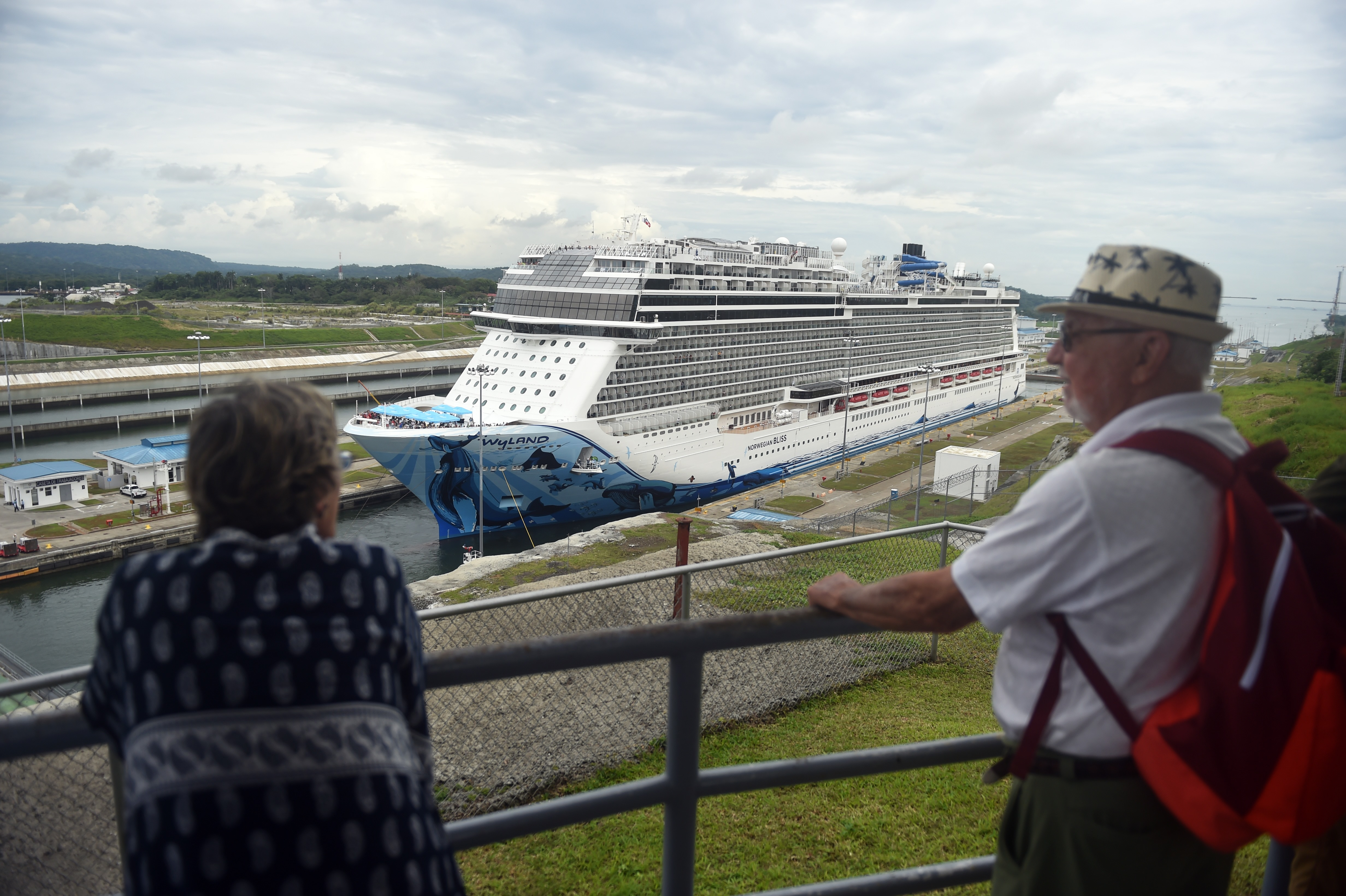 Tourists look at a cruise ship crossing the Panama Canal in the Agua Clara locks in Colon 80 km northwest from Panama City.